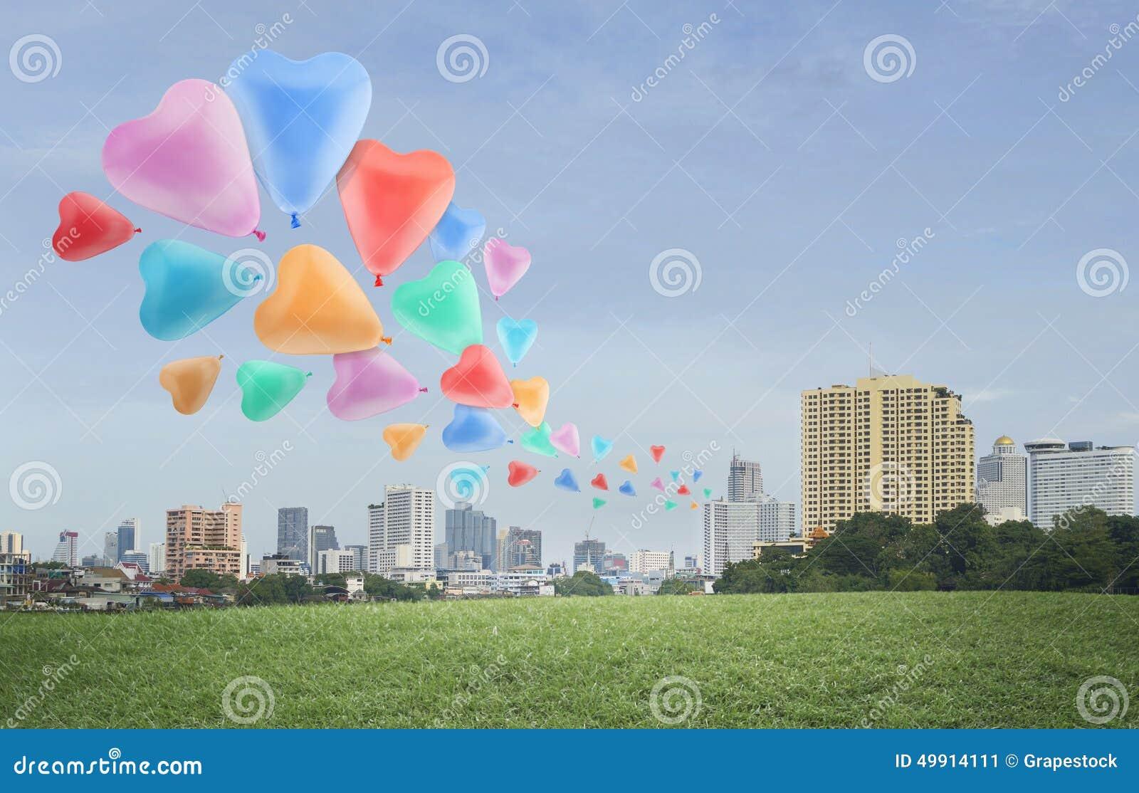 Kolorowy kierowy miłość balonu pławik na powietrzu przy miasta tłem