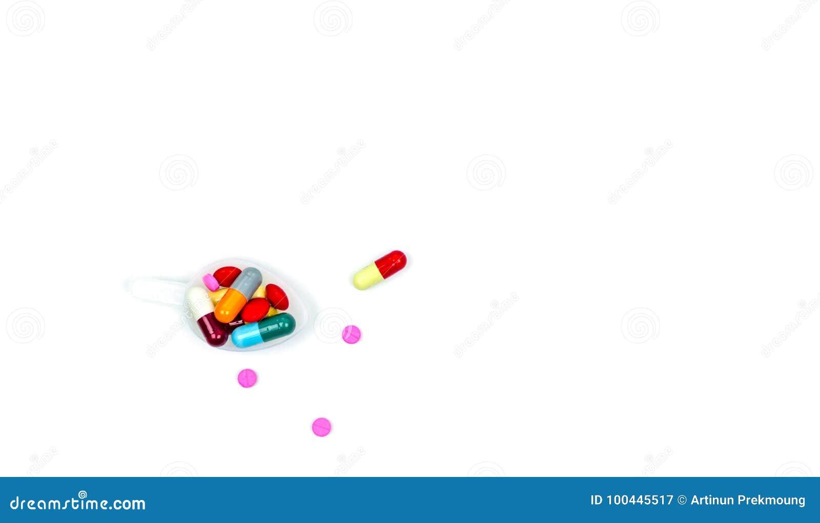 Kolorowy pigułki w plastikowym teaspoon i niektóre one pastylek i kapsuł rozprzestrzeniać na białym tle z kopii przestrzenią