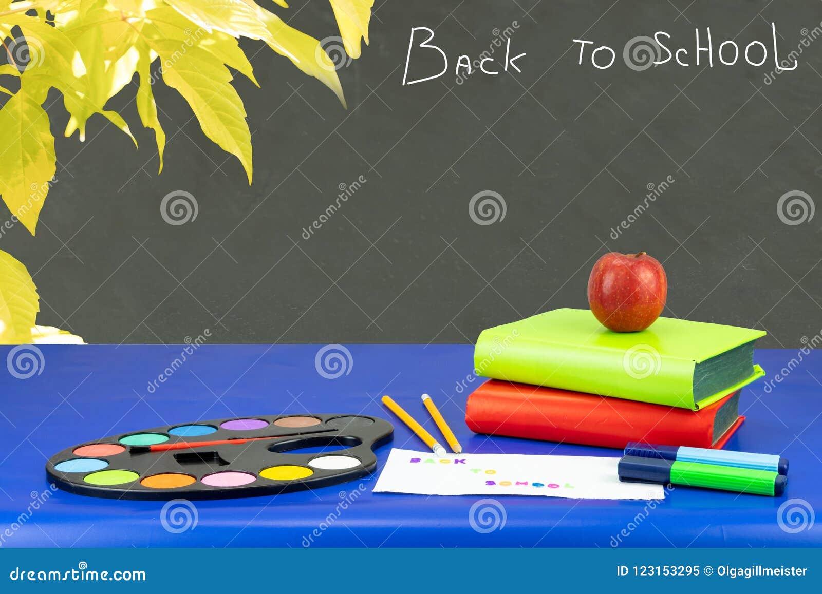 Kolorowy szkolny wyposażenie i dwa książki na zmroku - błękita stół znowu