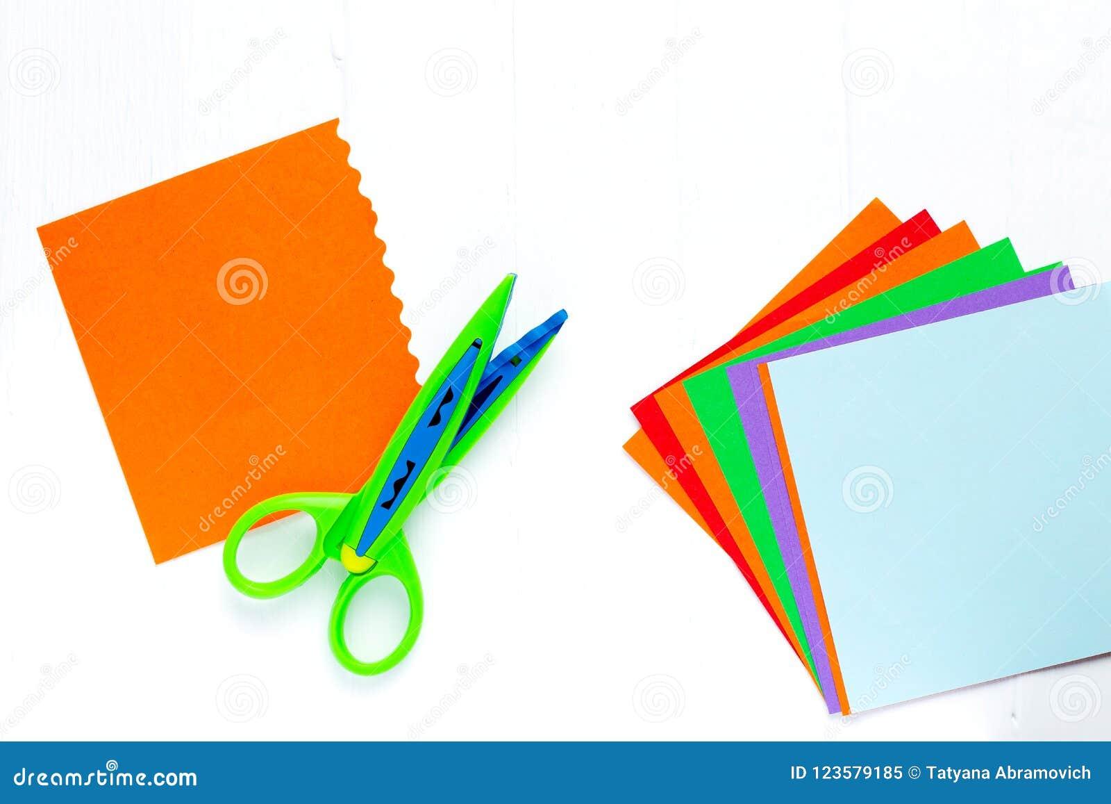 Koloru papier dla origami jest fan, nożyce z falistą krawędzią Na biel stole