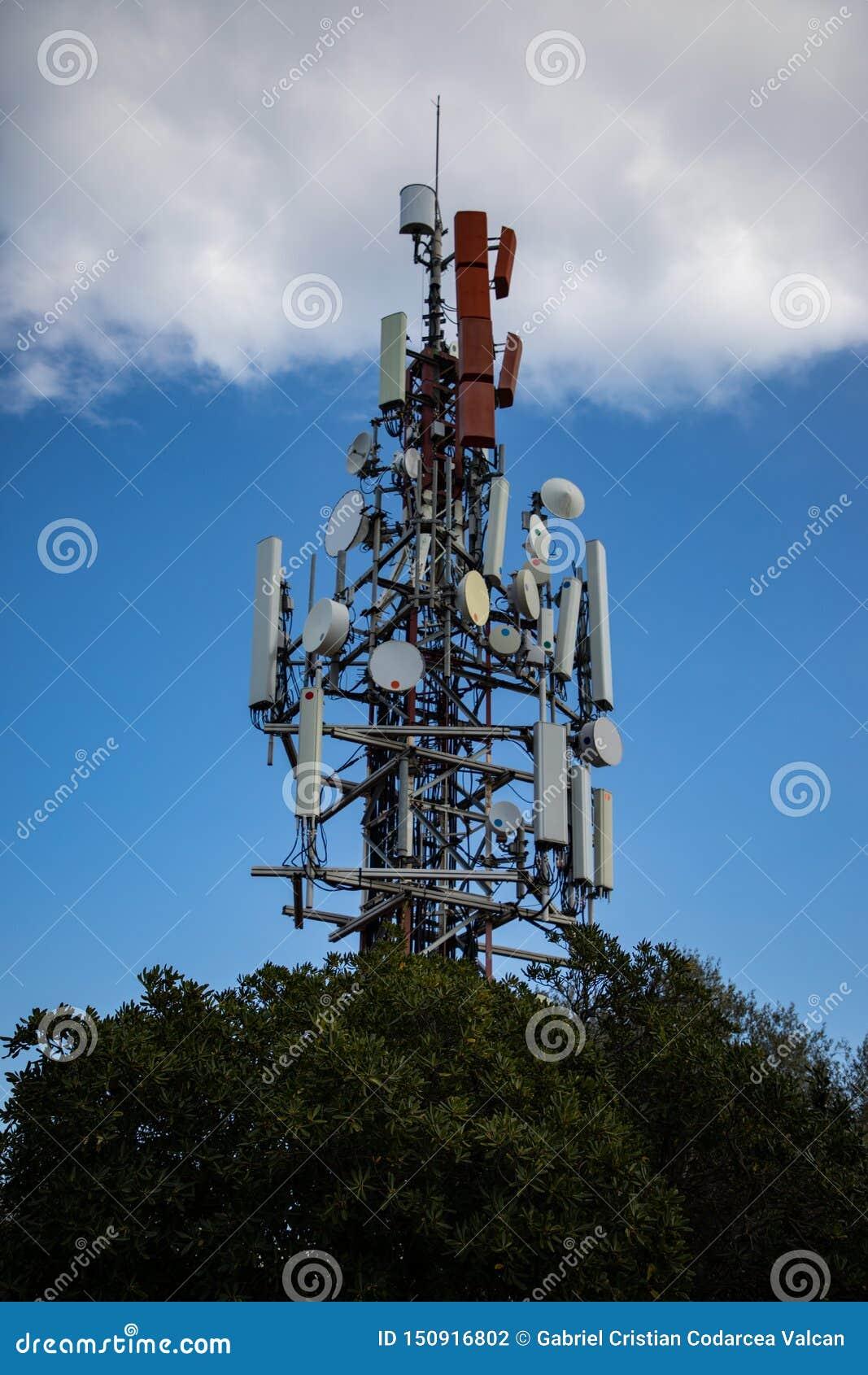 Komórki antena nad drzewem z chmurnym niebem