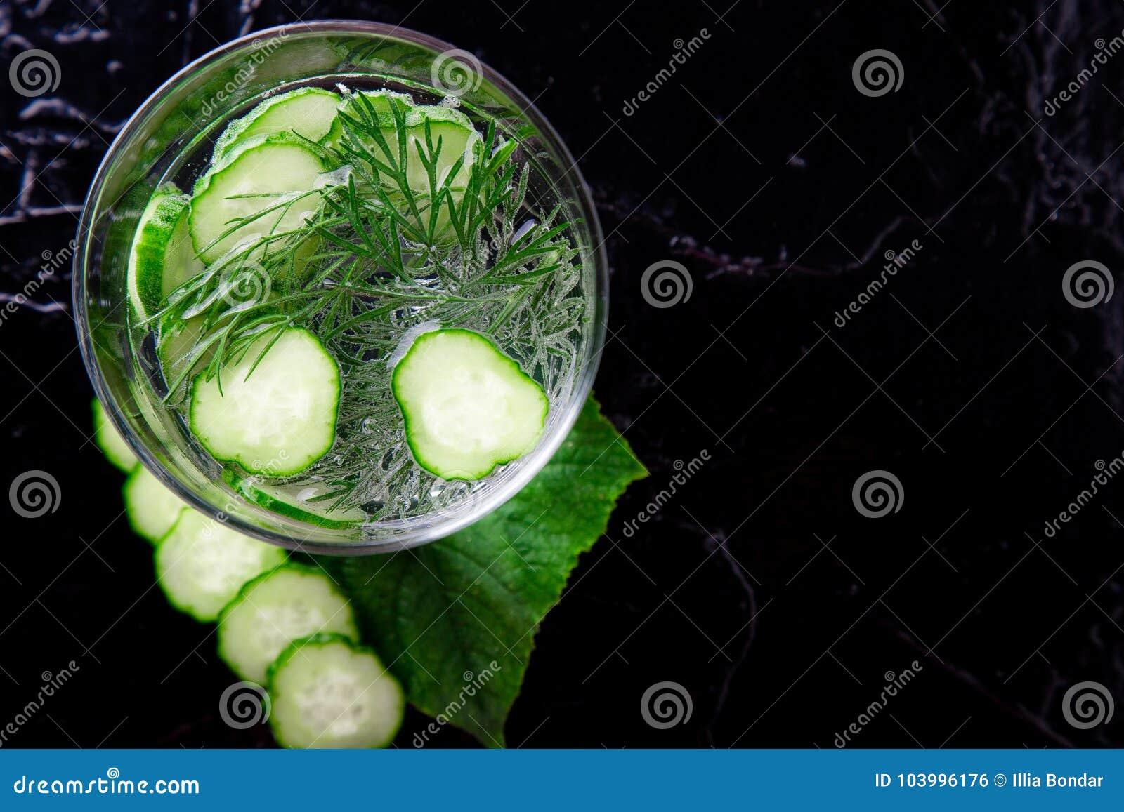 Komkommerwater in glas met dille op zwarte achtergrond Detox, dieet Backlight Hoogste mening De ruimte van het exemplaar