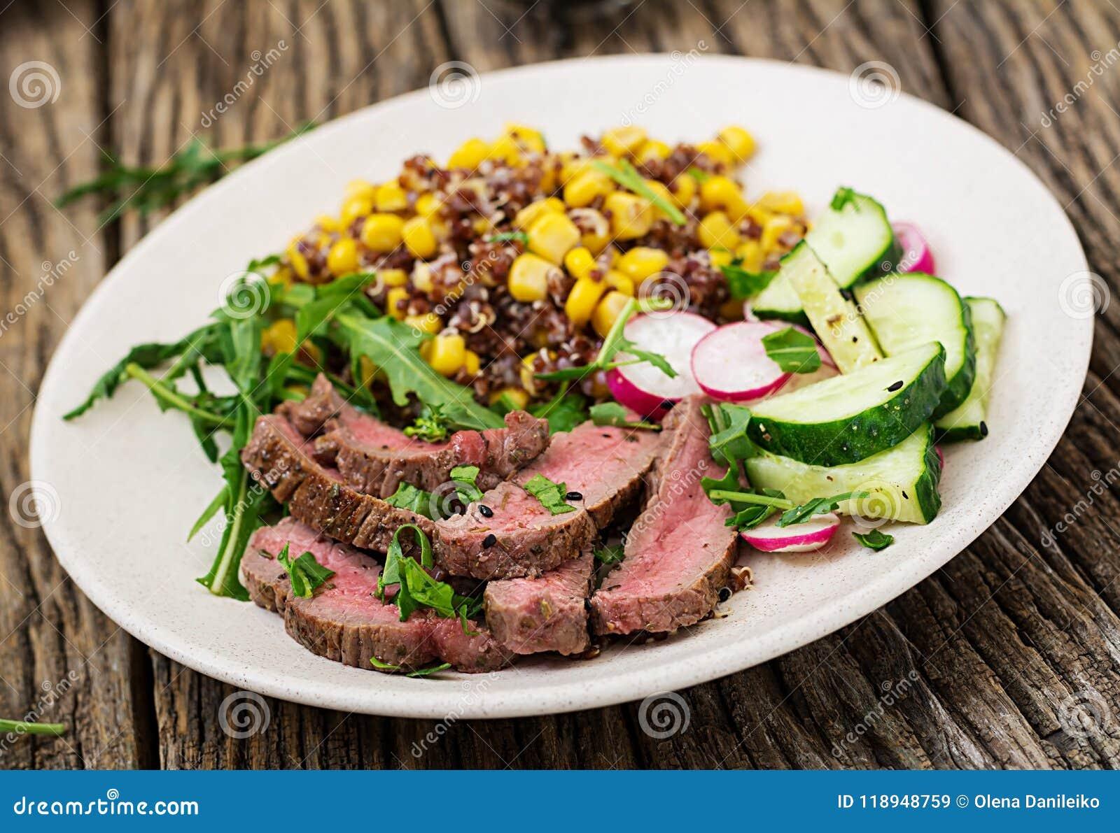 Komlunch met geroosterde rundvleeslapje vlees en quinoa, graan, komkommer, radijs en arugula