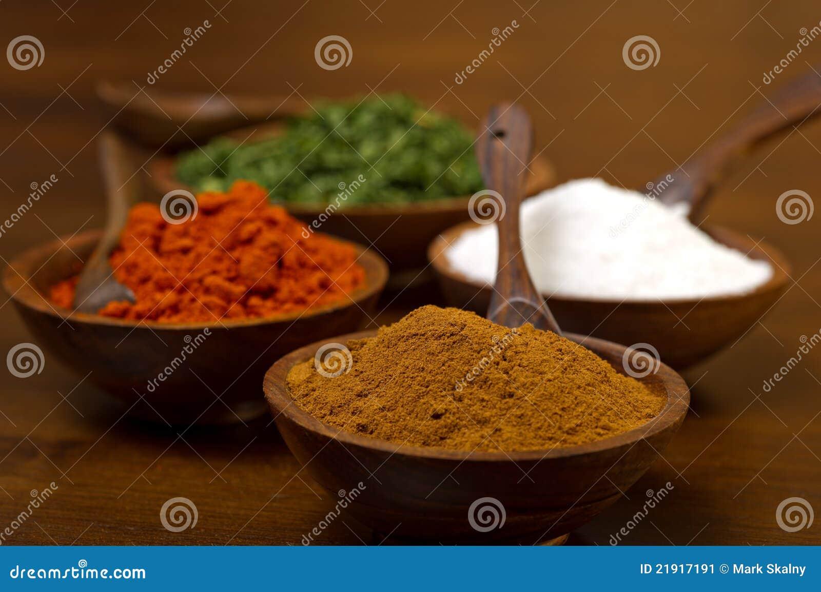 Houten kommen die met kleurrijke kruiden worden gevuld - de komijn, de ...