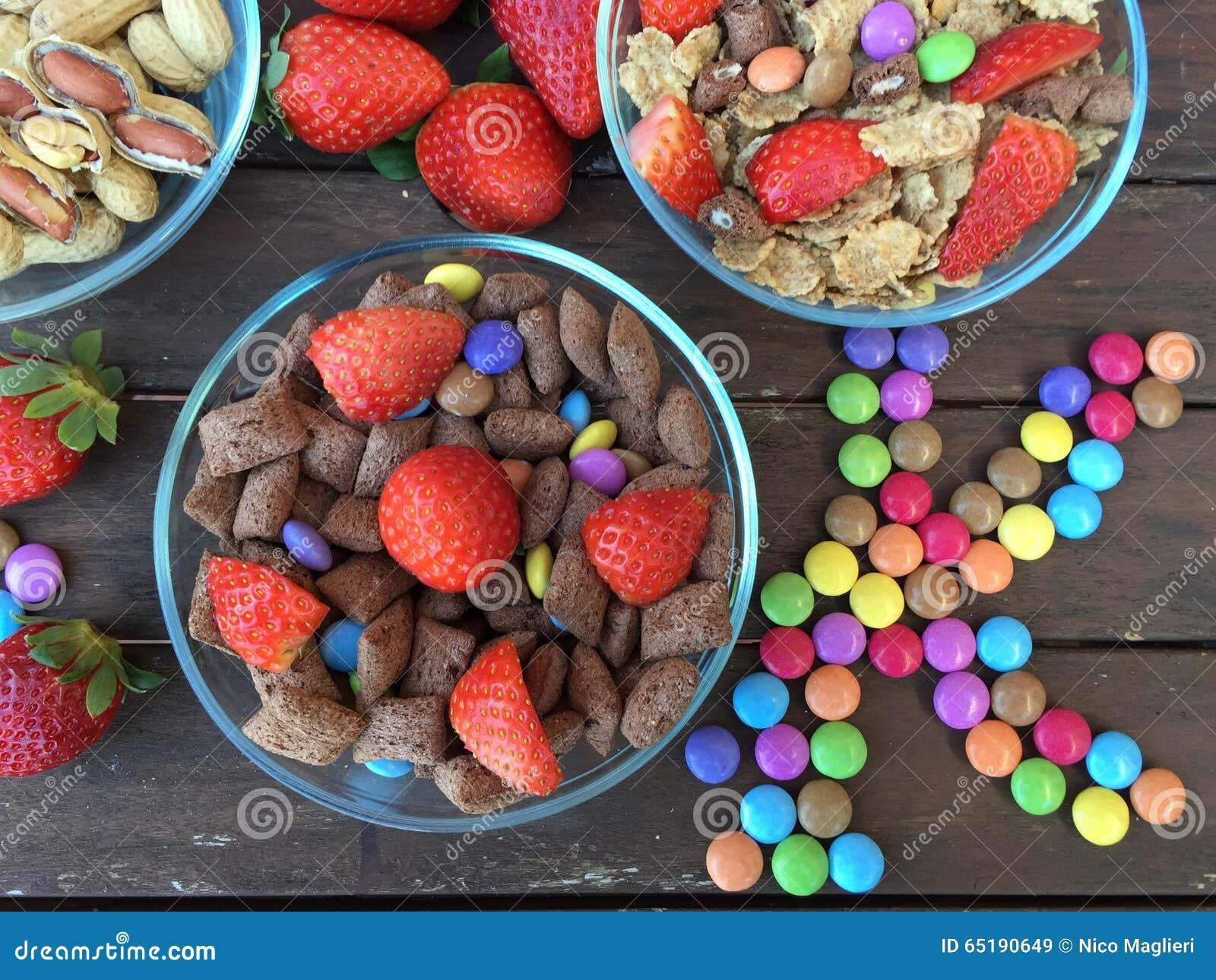 Kommen met Vlokken, aardbeien, pinda s en gekleurd suikergoed