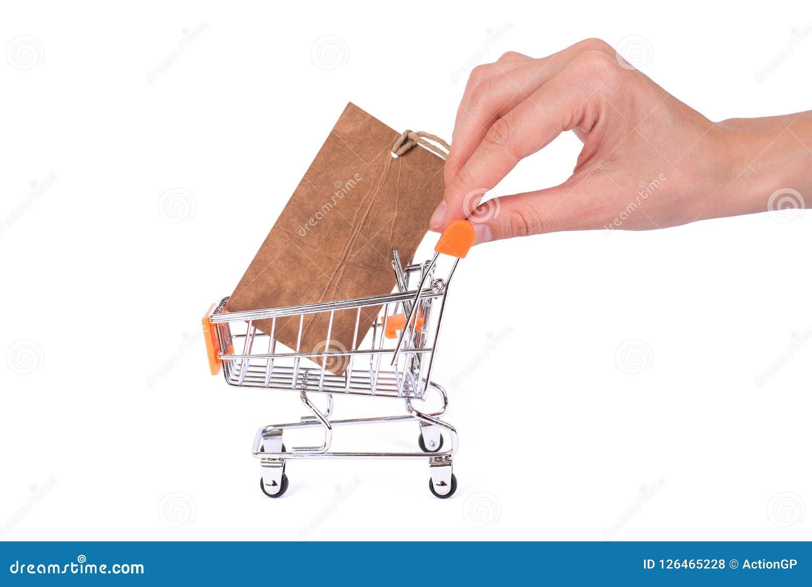 Kommersiellt consumerismbegrepp Sidoprofilslut upp fotoet av handkärran med pricetaginsidahanden som spela golfboll i hål den dri