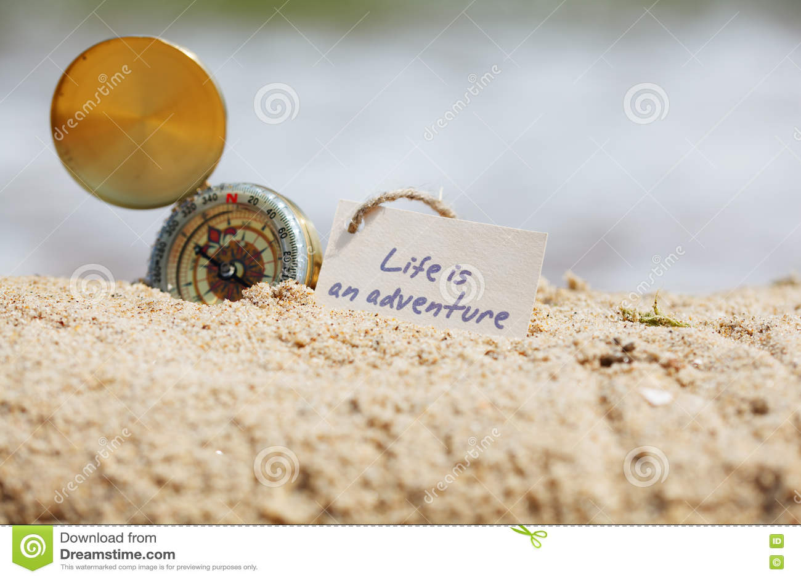 Kompas w piasku z wiadomością - życie jest przygodą