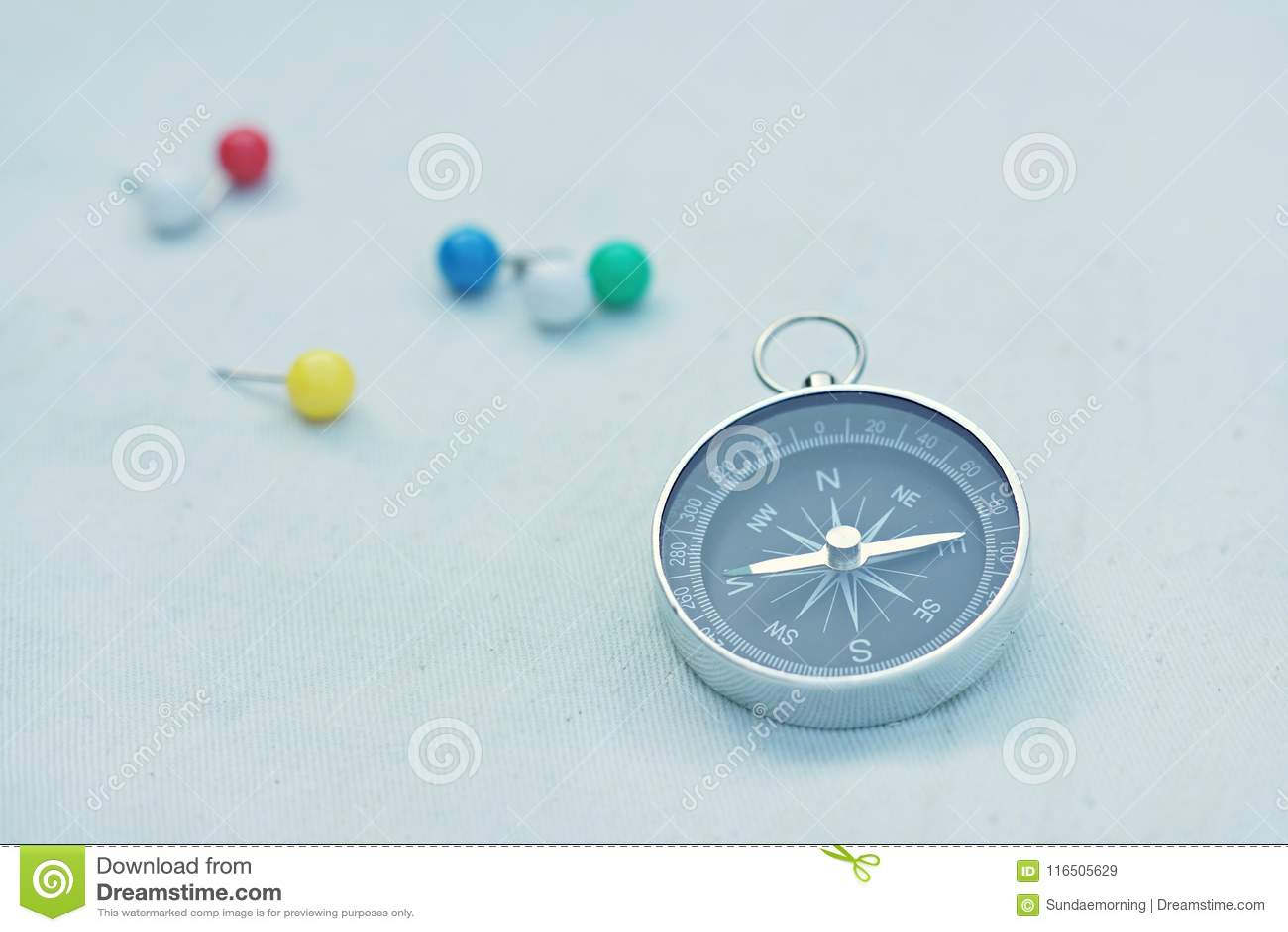 Kompasu i ocechowania szpilki na brezentowym tle