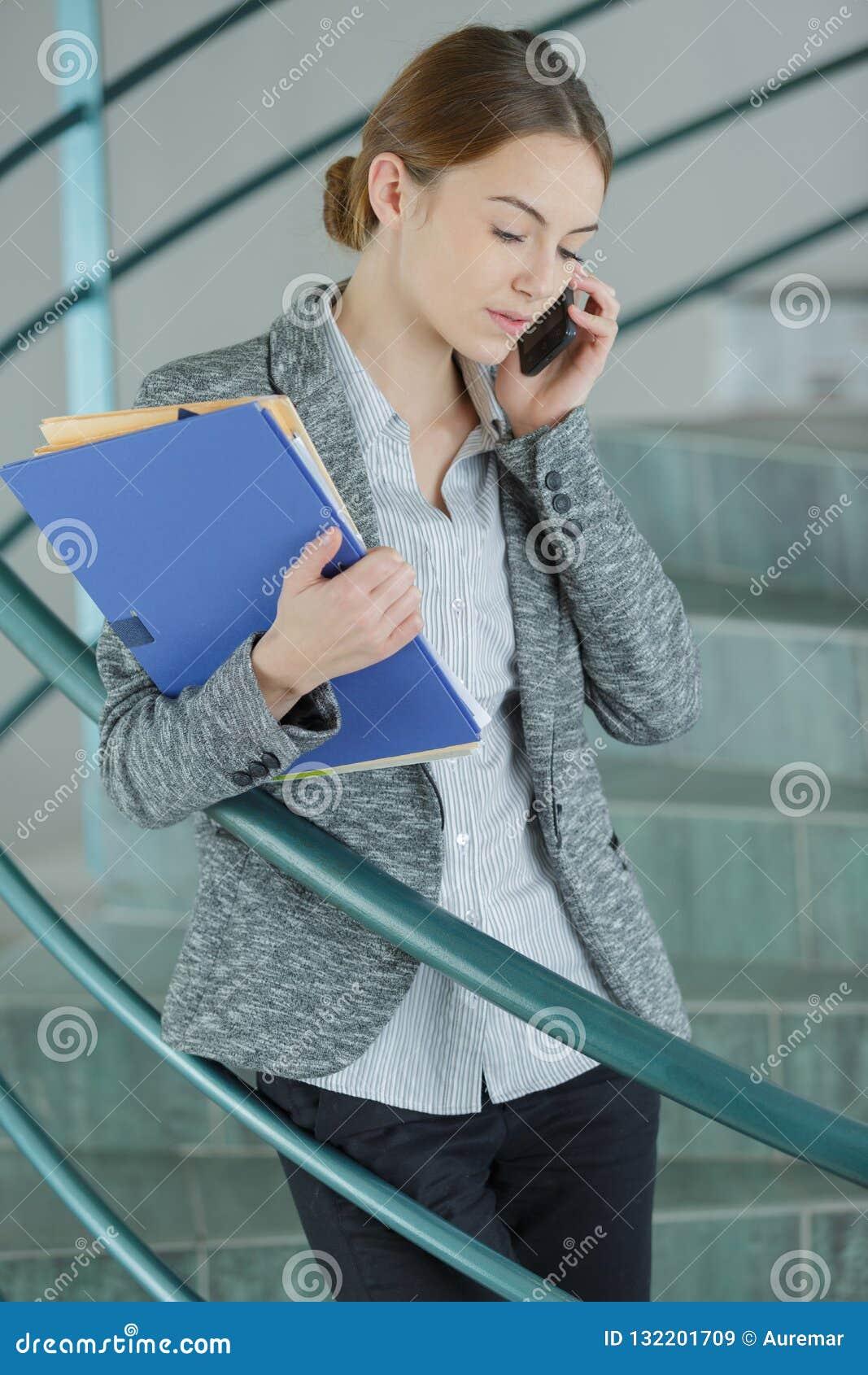 Kompetent kvinnlig arbetare som använder celltelefonen
