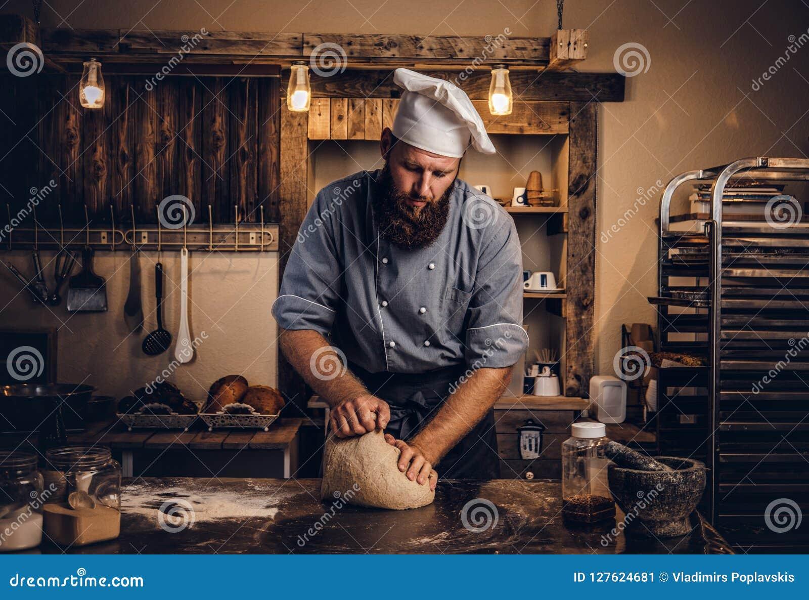 Koncentrerad kock som knådar deg i köket