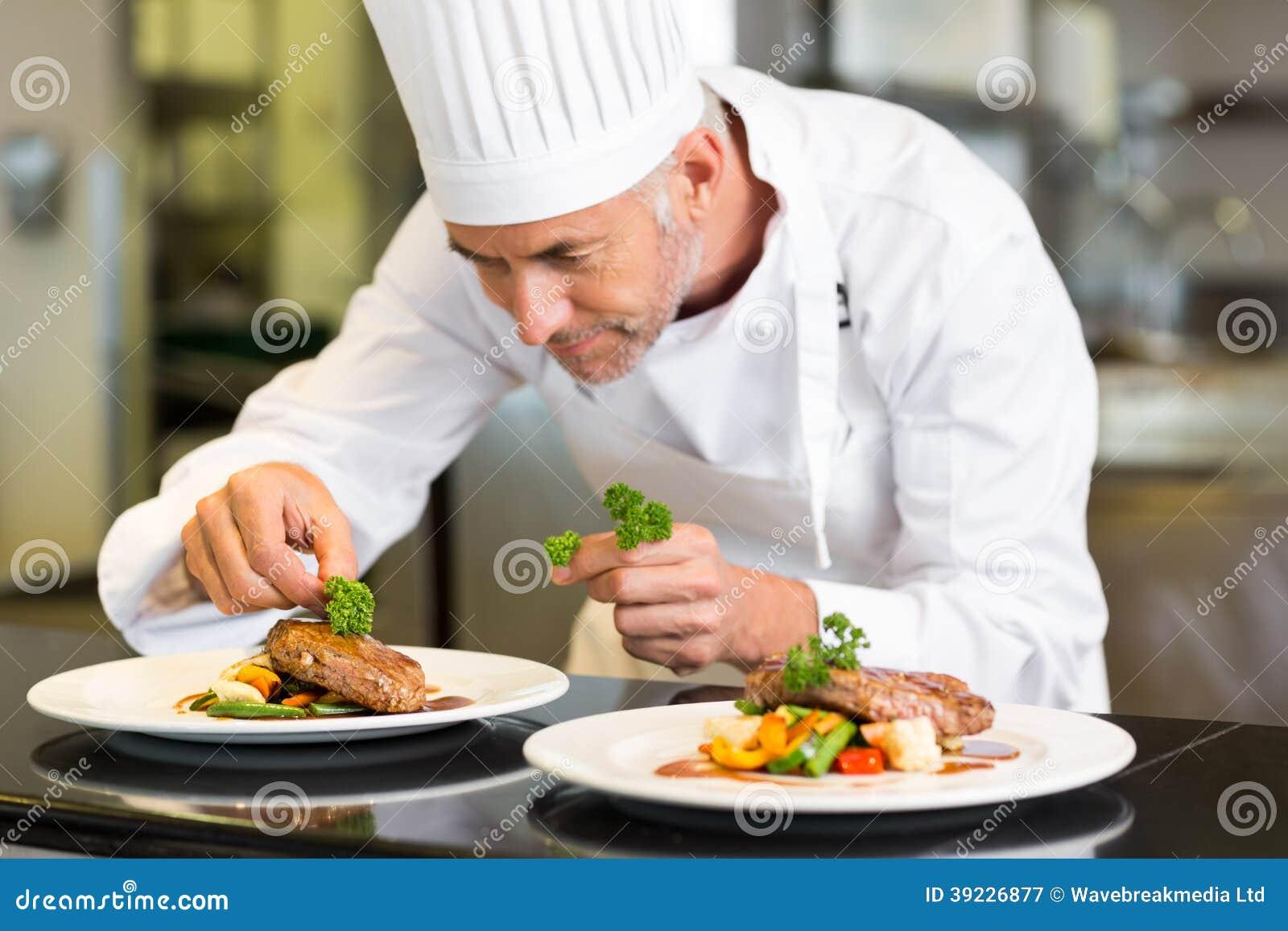 Koncentrerad manlig kock som garnerar mat i kök
