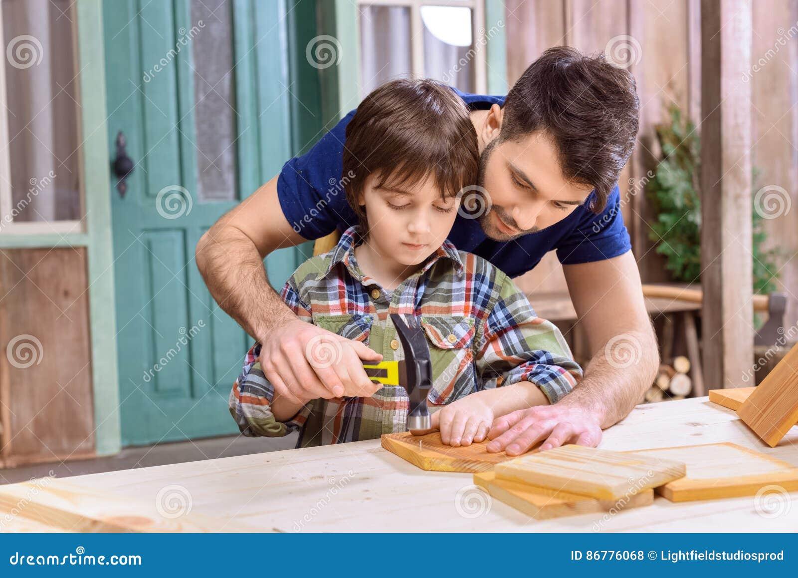 Koncentrerade sonen för fadern spikar den undervisning till att bulta i träplanka