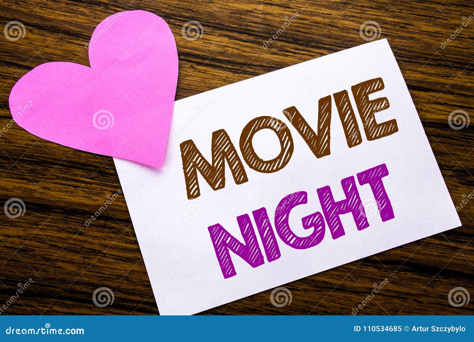 Konceptualny ręki writing tekst pokazuje film noc Pojęcie dla Wathing filmów pisać na kleistym nutowym papierze, drewniany drewni
