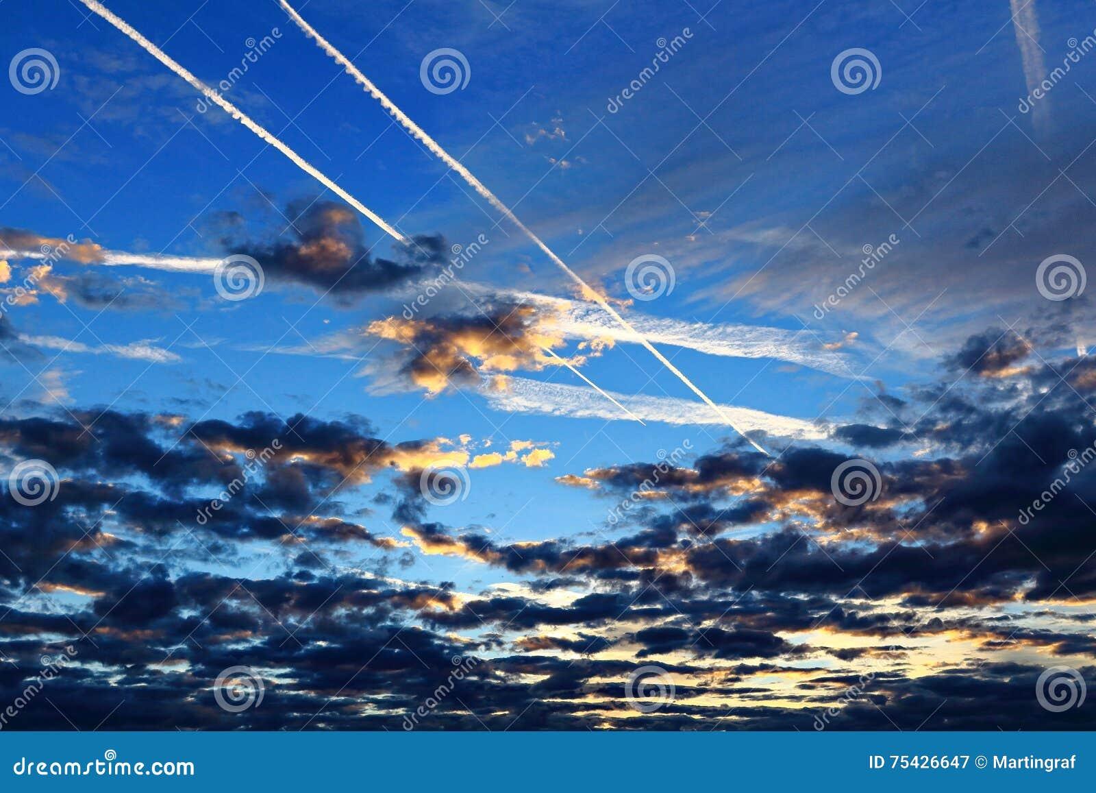Kondensstreifen über Wolken bis zum blauer Stunde