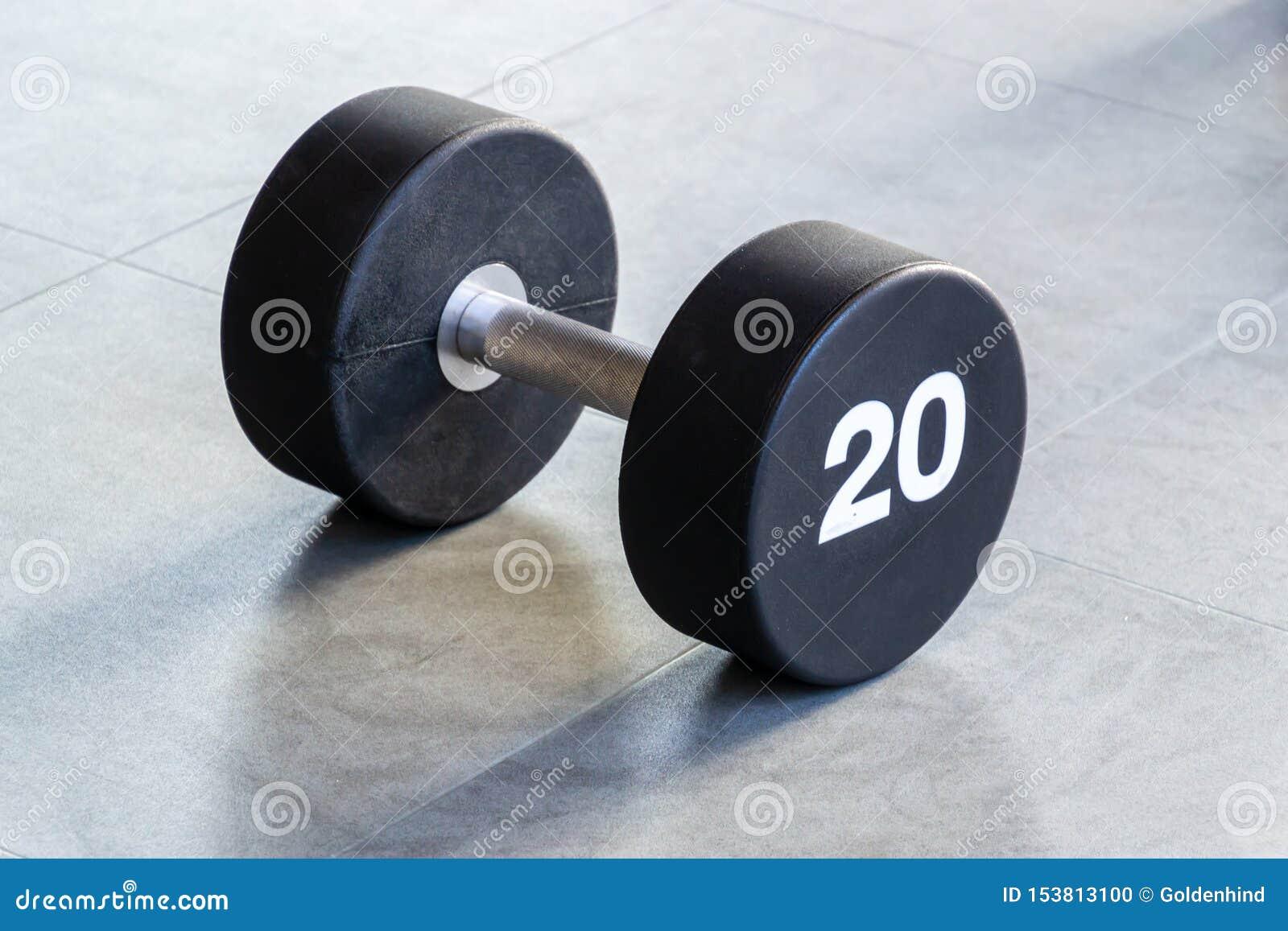 Kondition- eller bodybuildingbegreppsbakgrund Svart järnhantel på golvet i idrottshallen