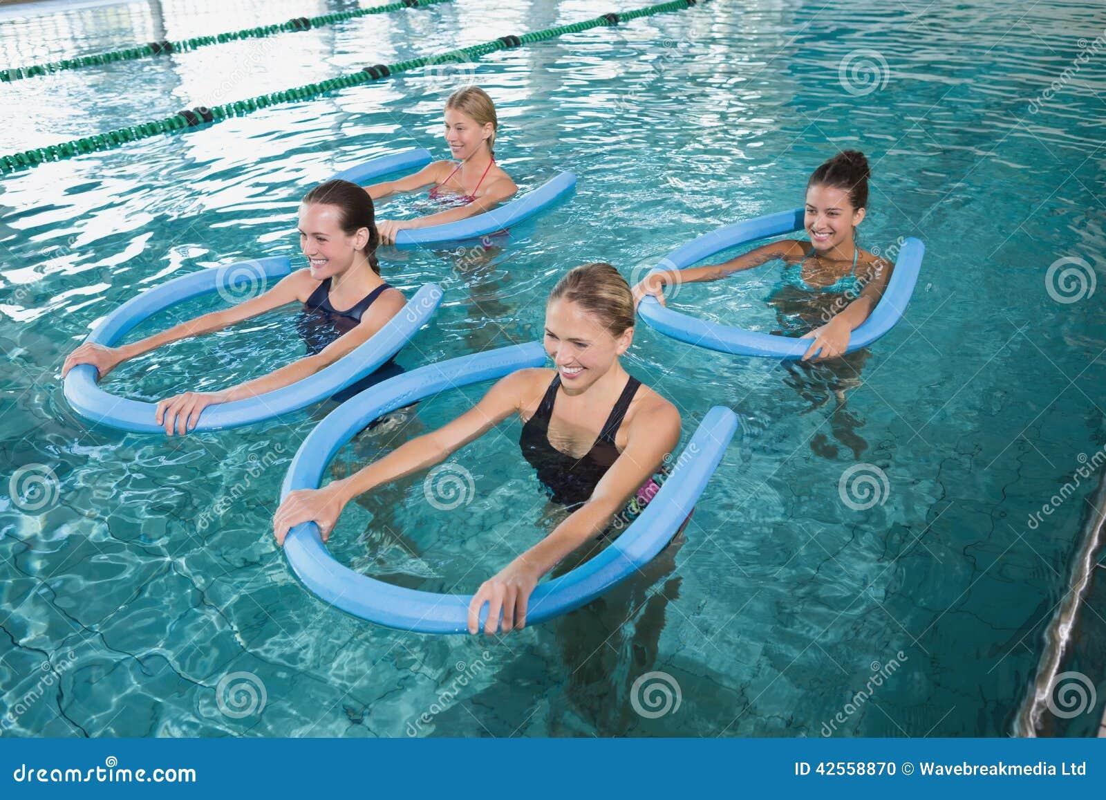 Konditiongrupp som gör aquaaerobics med skumrullar
