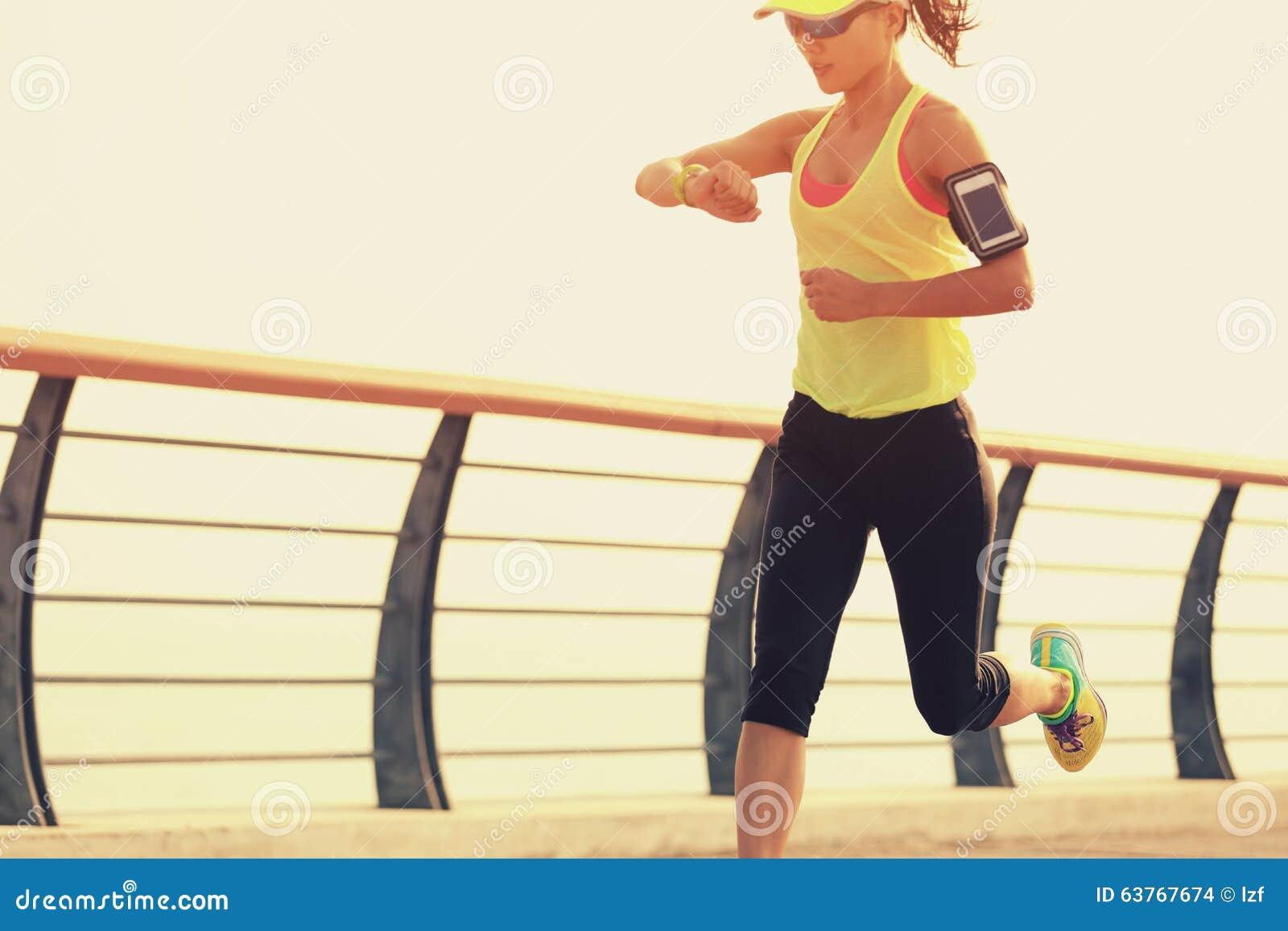 Konditionkvinnalöpare som kontrollerar hennes rinnande tid från den smarta klockan på sjösidan