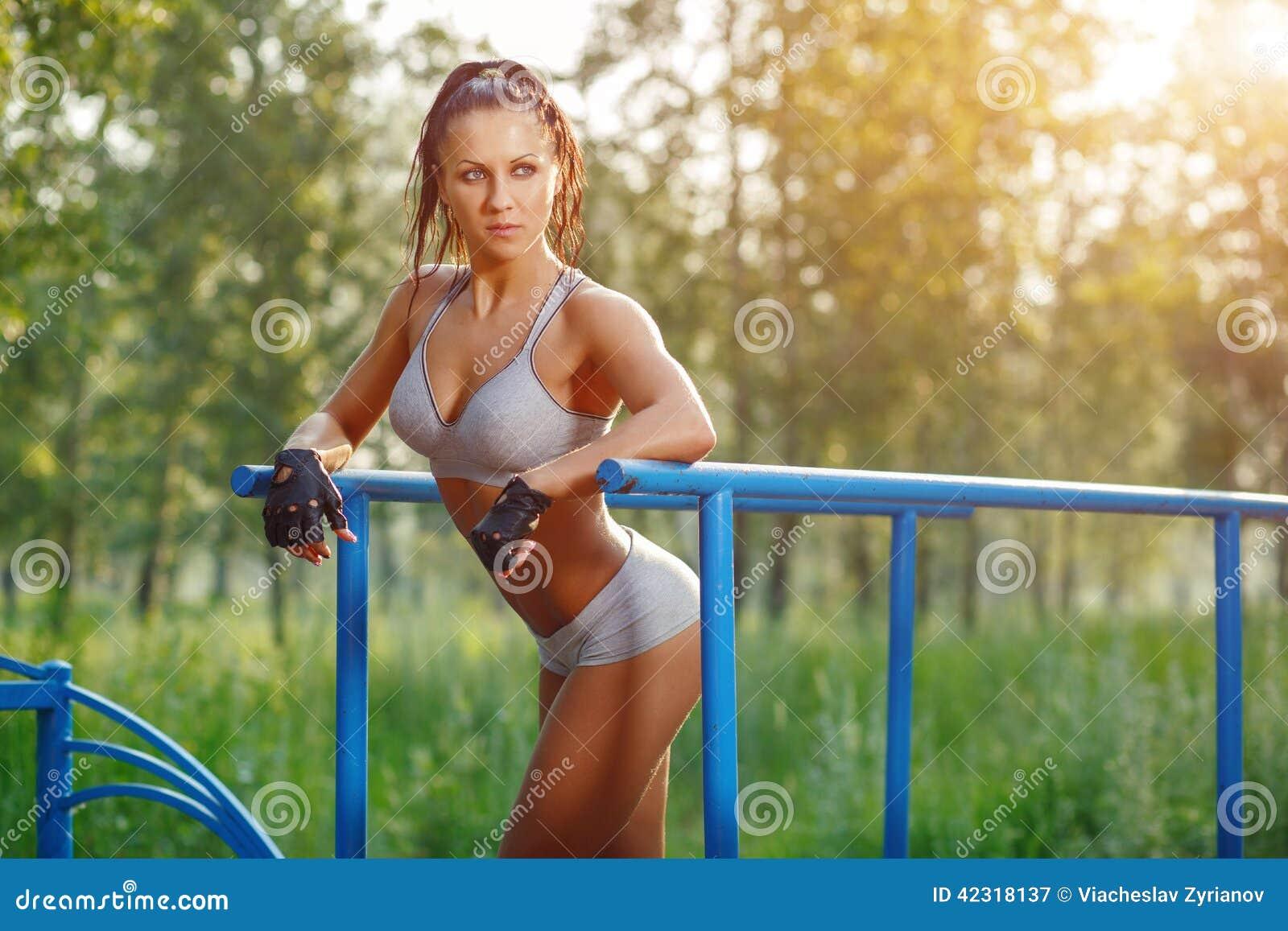 Konditionkvinnan kopplar av, efter genomköraren har övat på utomhus- stänger