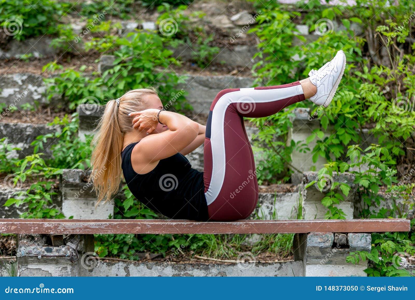 Konditionlivsstil Ung kvinna som v?rmer upp p? en b?nk som g?r ?vningar p? buk- muskler Sportig ung blond flicka p? ett soligt