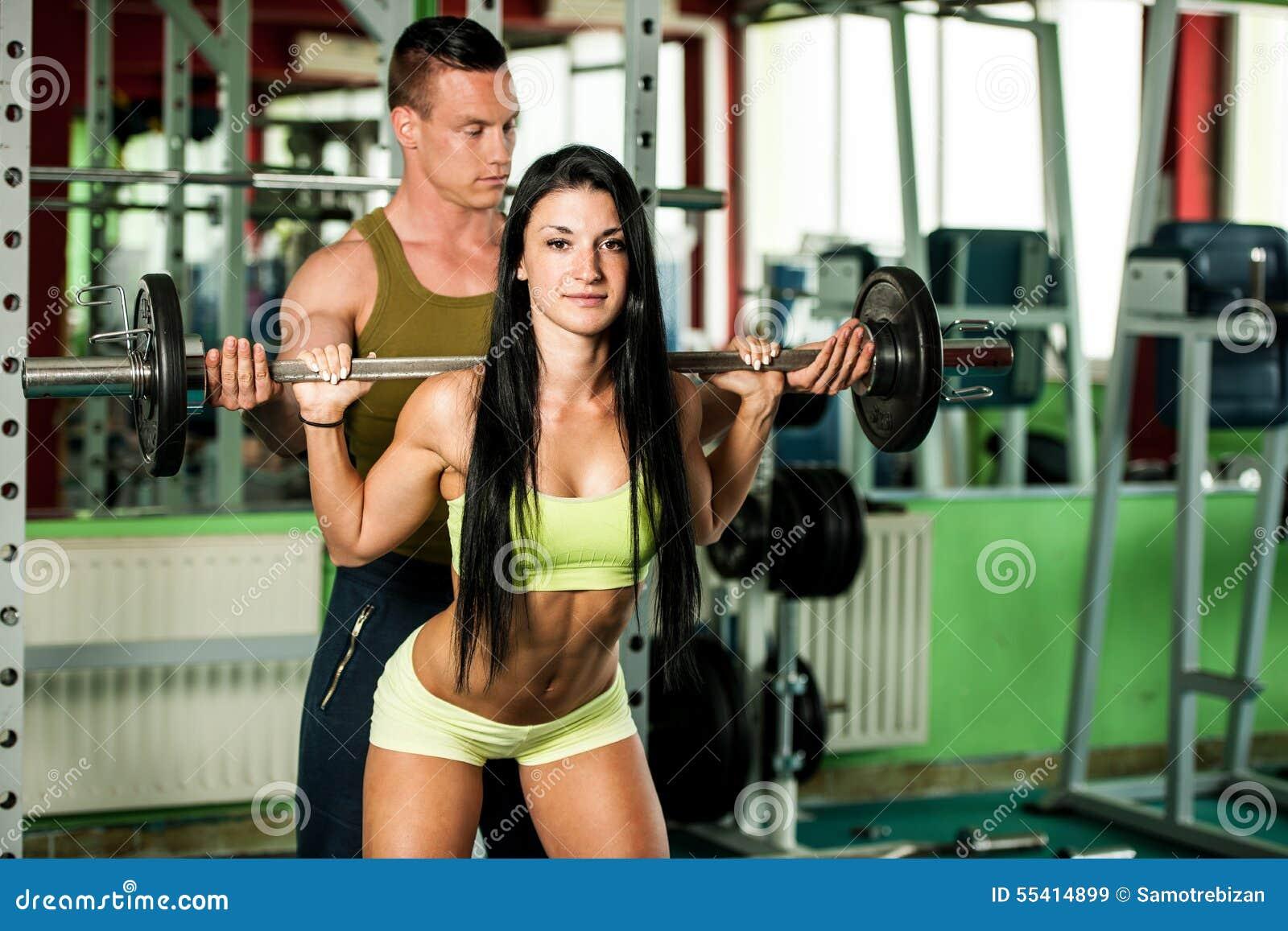 Konditionyouplegenomkörare - färdiga mann och kvinnan utbildar i idrottshall