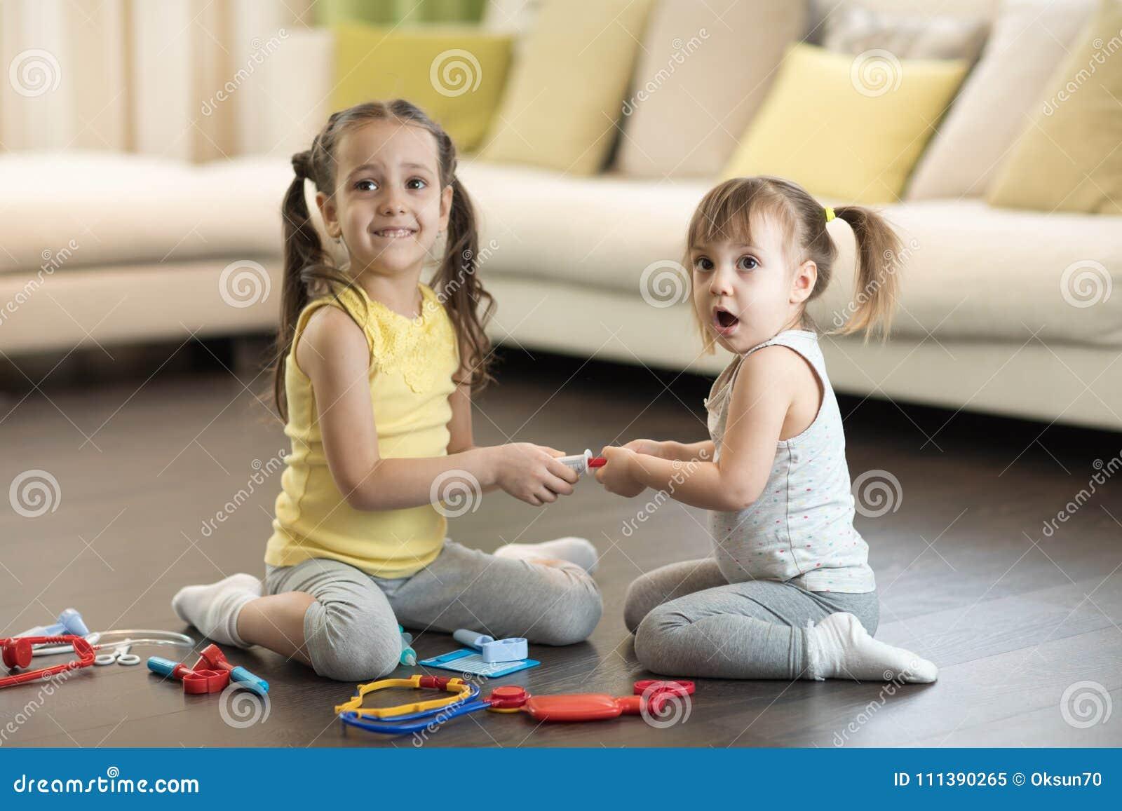 Konflikt mellan små systrar Ungar slåss, litet barnflickatagande leksaken, siblingförhållanden