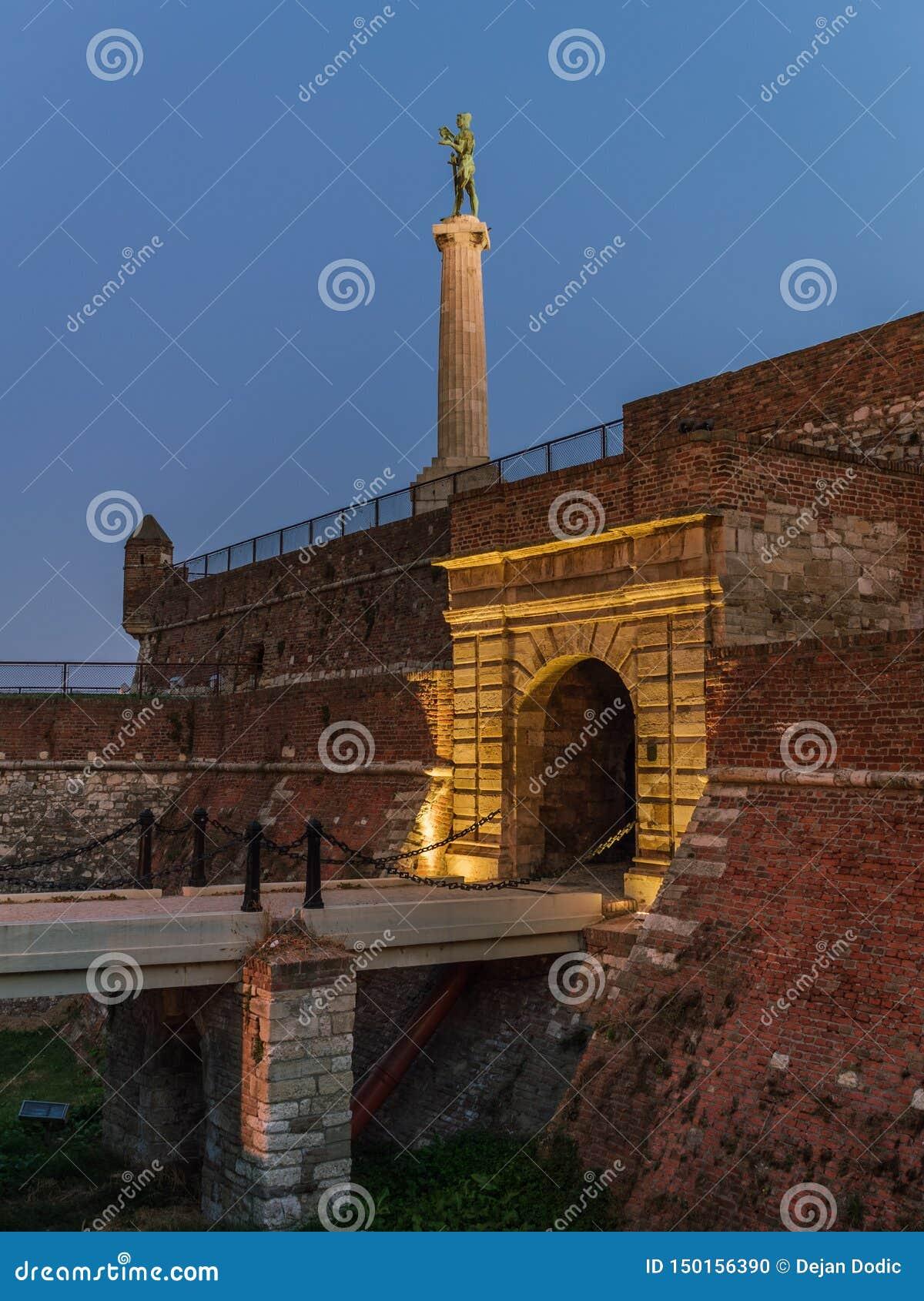 Koningspoort in Kalemegdan, Belgrado, Servië, met het Kampioenstandbeeld op achtergrond bij nacht