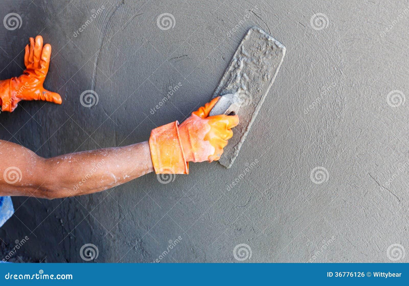 Konkret arbetare för stuckatör på väggen av huskonstruktion