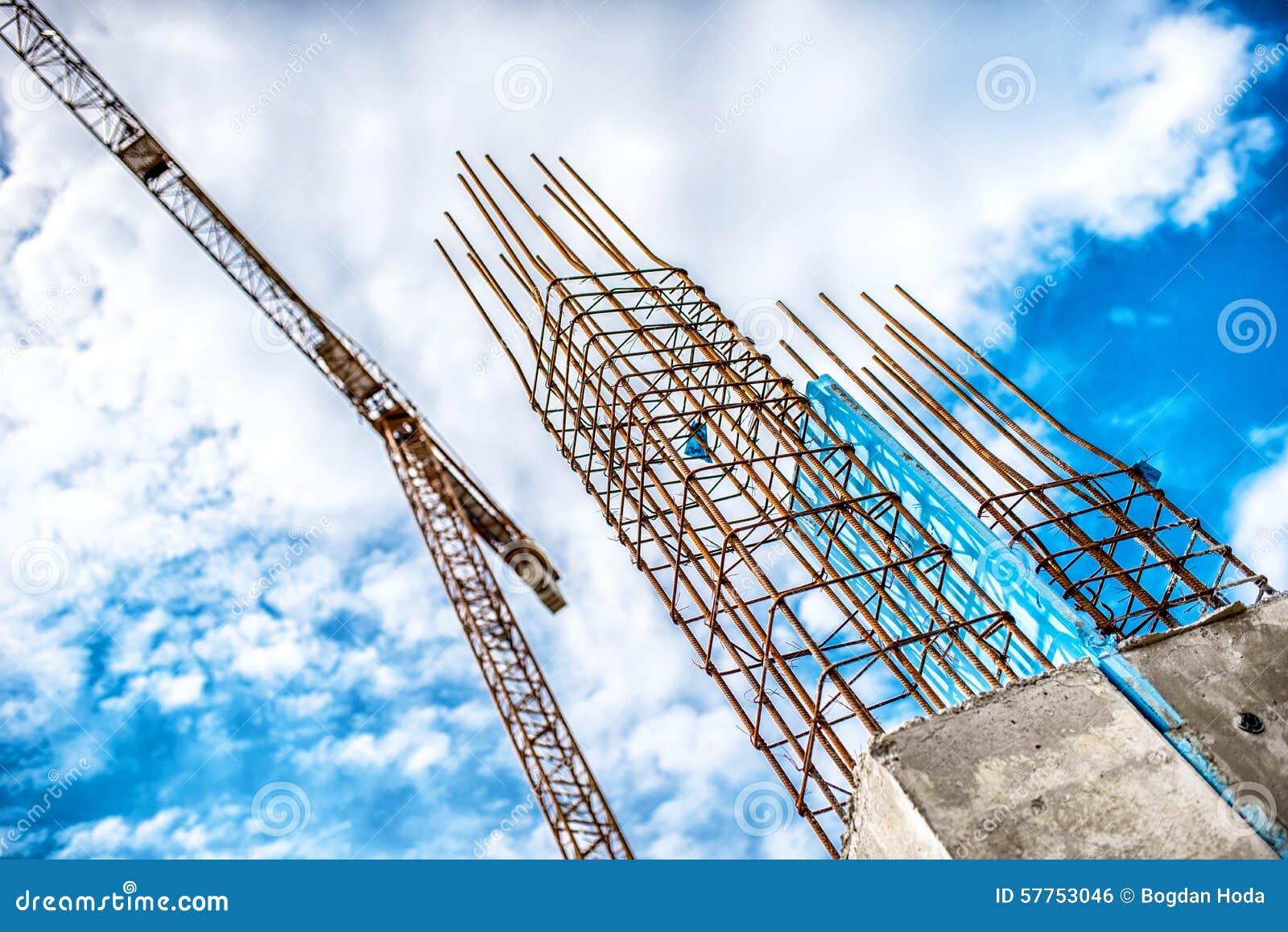 Konkrete Säulen auf Industriebaustandort Gebäude des Wolkenkratzers mit Kran, Werkzeugen und Bewehrungsstahlstangen