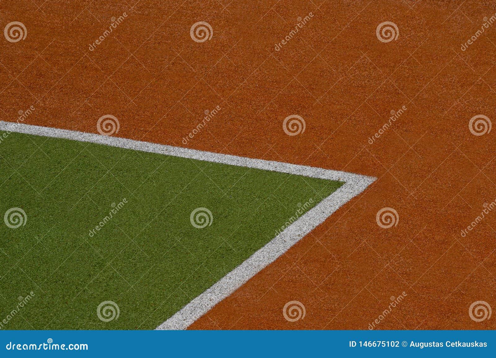 Konstgjord gräsplan och brun torvatexturbakgrund med den vita linjen fläckar