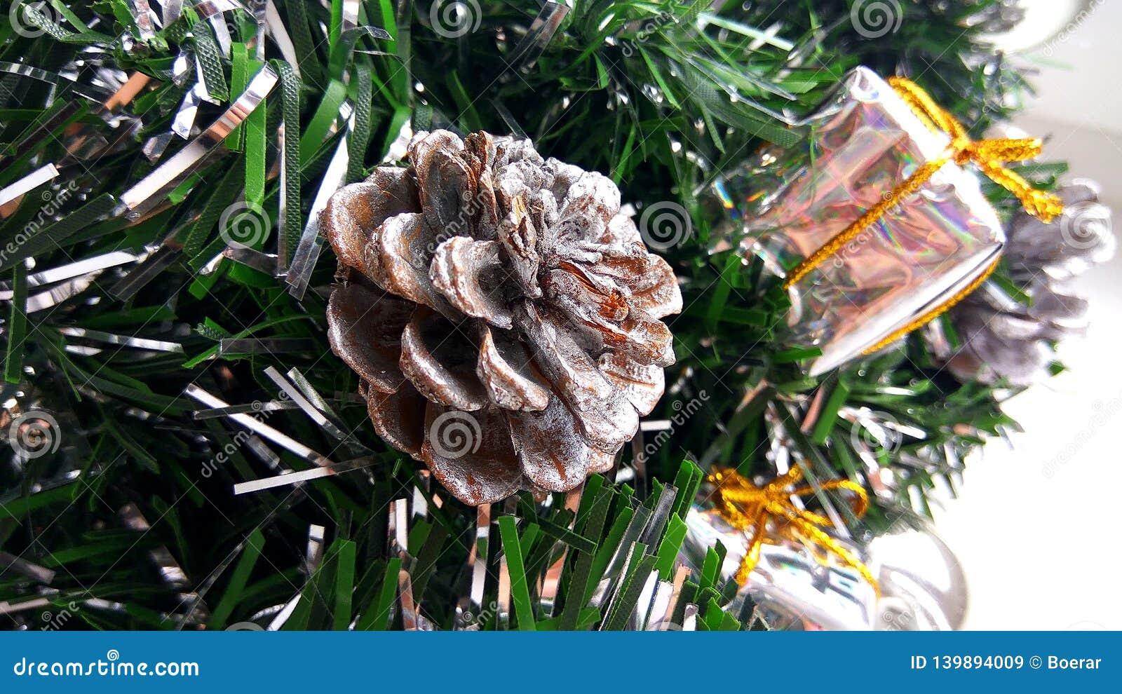 Konstgjorda julgranfruncher som dekoreras med silverstruntsaker, leksakgåvaaskar och kotten Feriedecorati för nytt år