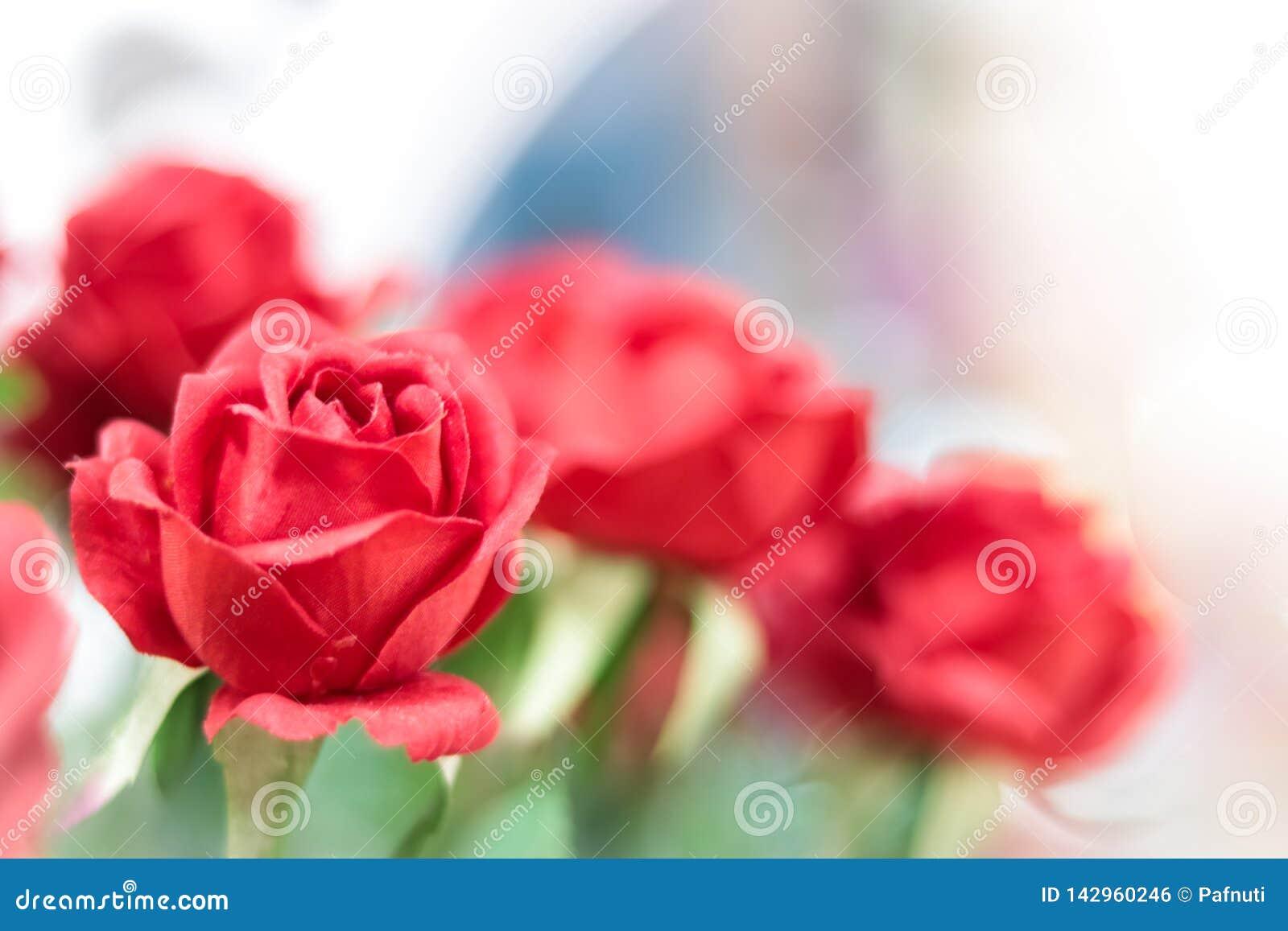 Konstgjorda röda rosor på suddig bakgrund