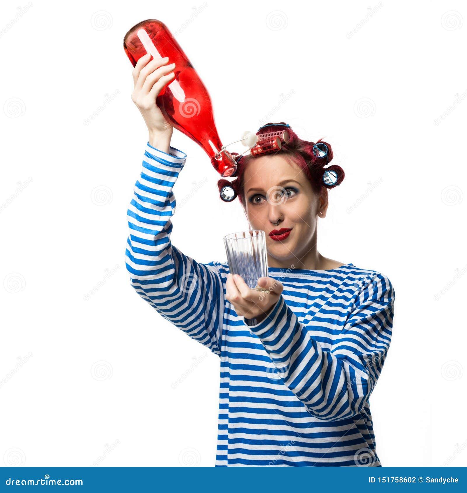 Konstig hemmafru som rymmer en tomglas av vin och exponeringsglas på en vit bakgrund Kvinnlig alkoholböjelse för begrepp