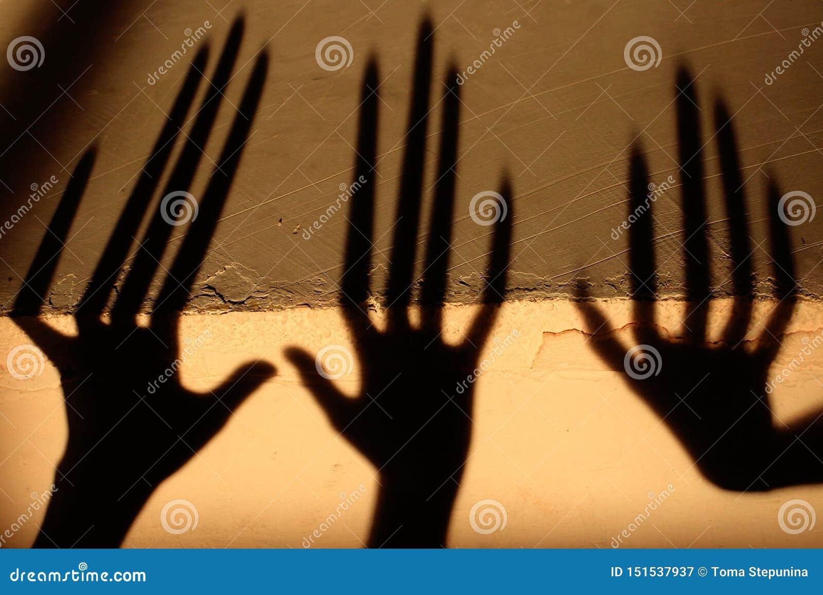 Konstig skugga p? v?ggen Ruskig skugga abstrakt bakgrund Svart skugga av en stor hand p? v?ggen Kontur av en hand på T