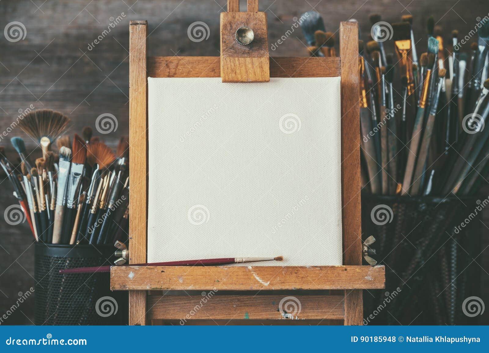 Konstnärlig utrustning i en konstnärstudio: tomma konstnärkanfas och borstar