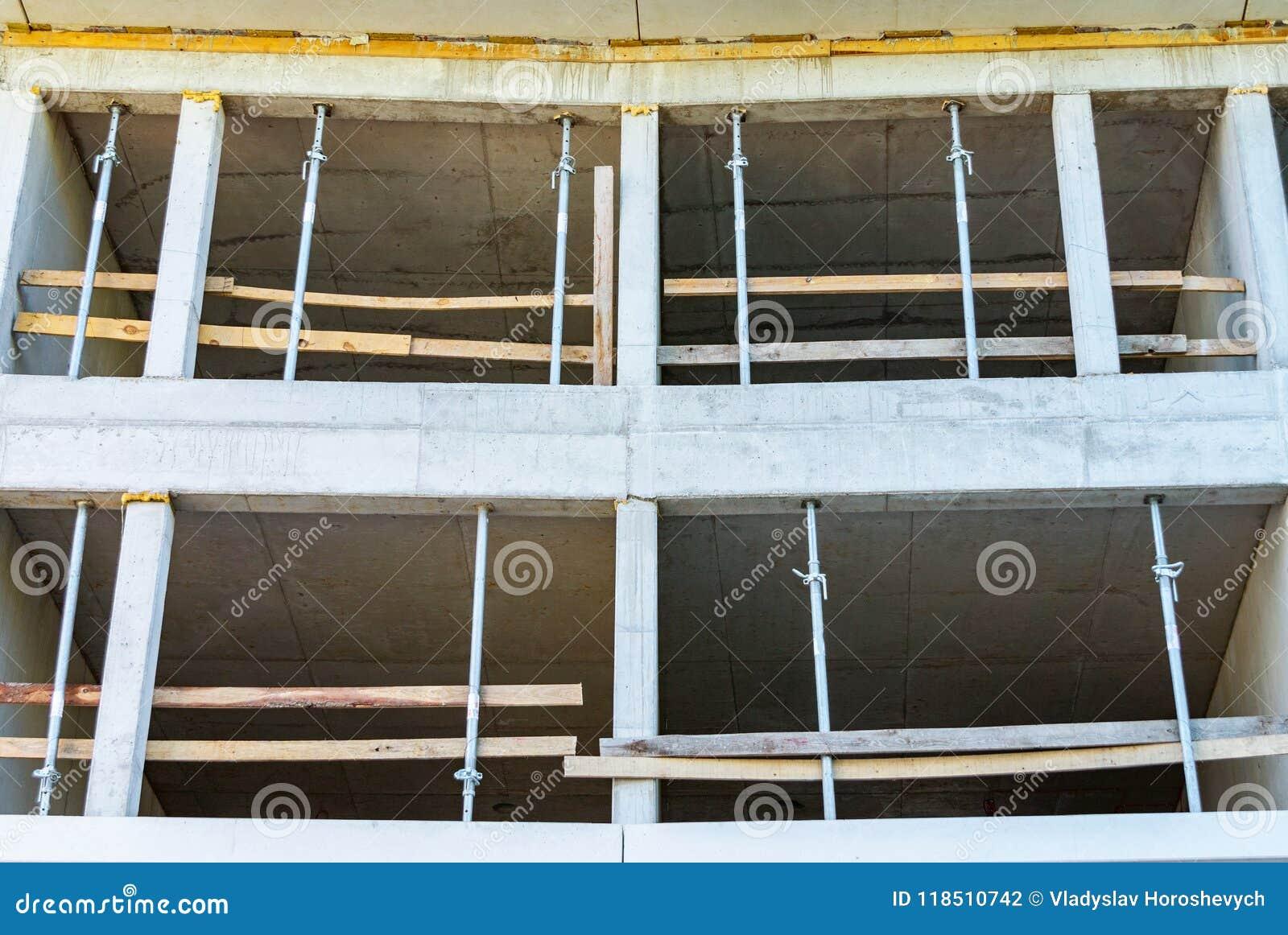 Konstruktion av ett monolitiskt hus som göras av betong, konkret service, formwork och kuggar