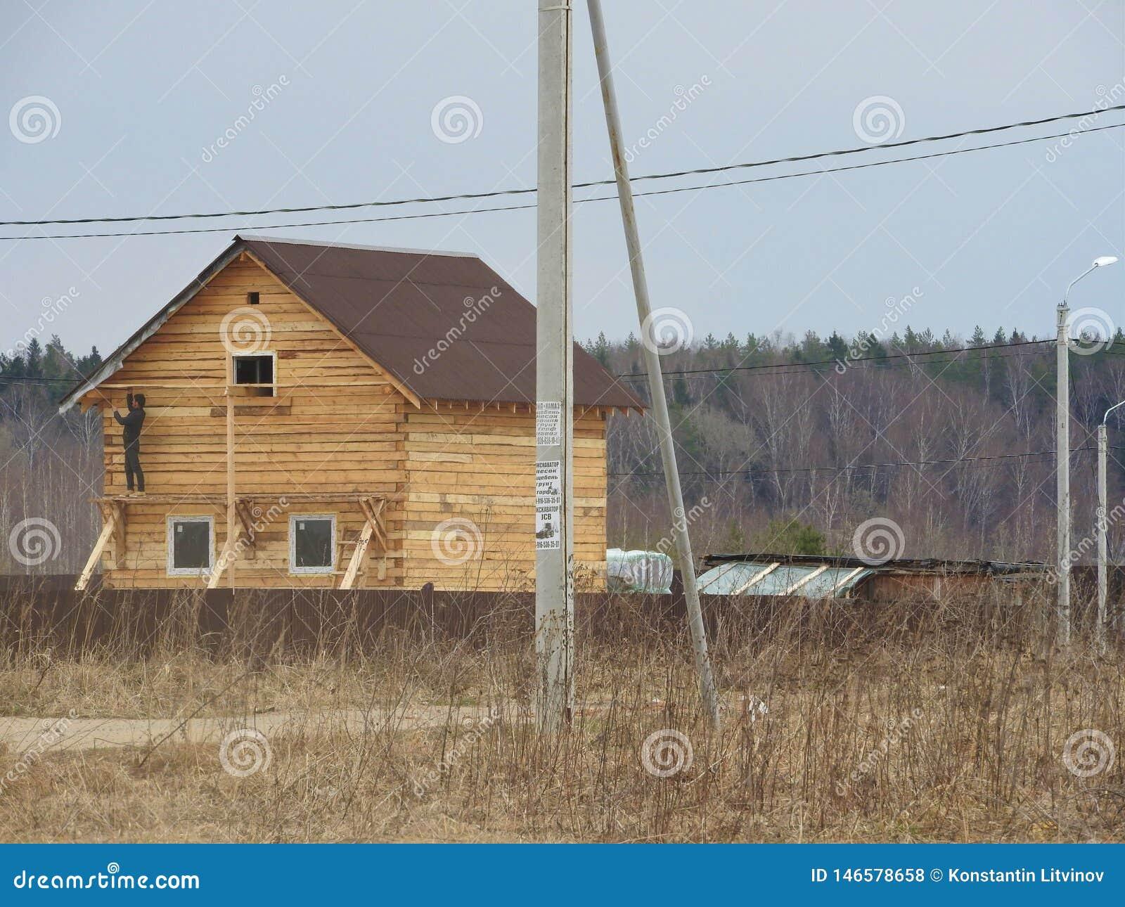 Konstruktion av huset från en stång, mannen arbetar Stugan göras av pläterat trä Installation av ramen av