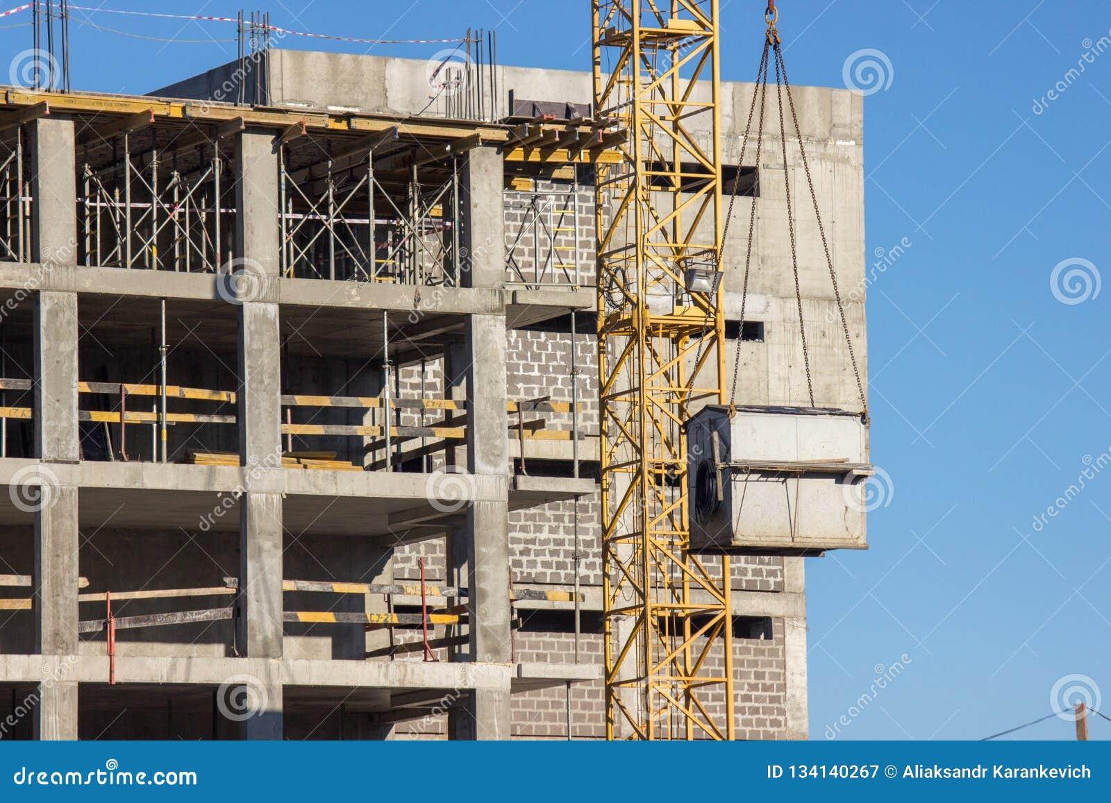 Konstruktion av ram-betong hyreshus med en höghuskran Lyft skjulet upp på bakgrunden av det oavslutat