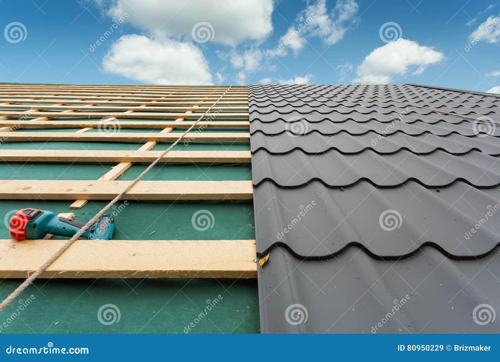 Konstruktionshus under Tak med metalltegelplattan, skruvmejsel och takläggajärn