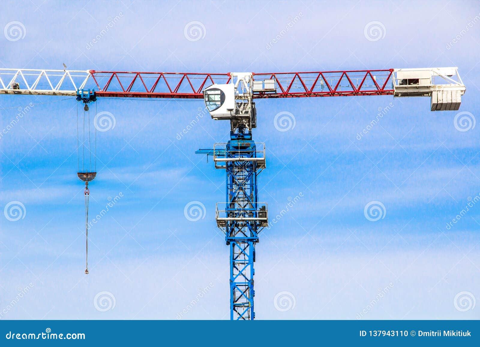 Konstruktionskran för hög elevator med vita, röda och blåa färger mot en blå himmel