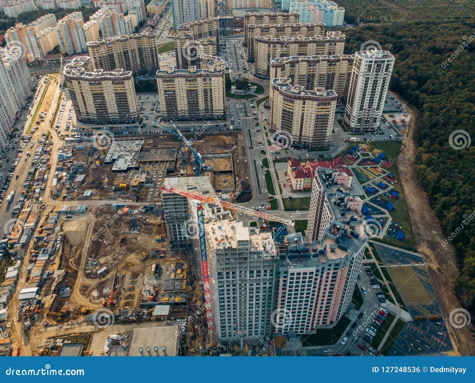 Konstruktionsplats med byggnadskranar och annan utrustning, industriella byggda eller för godsutveckling moderna byggnader, flyg-