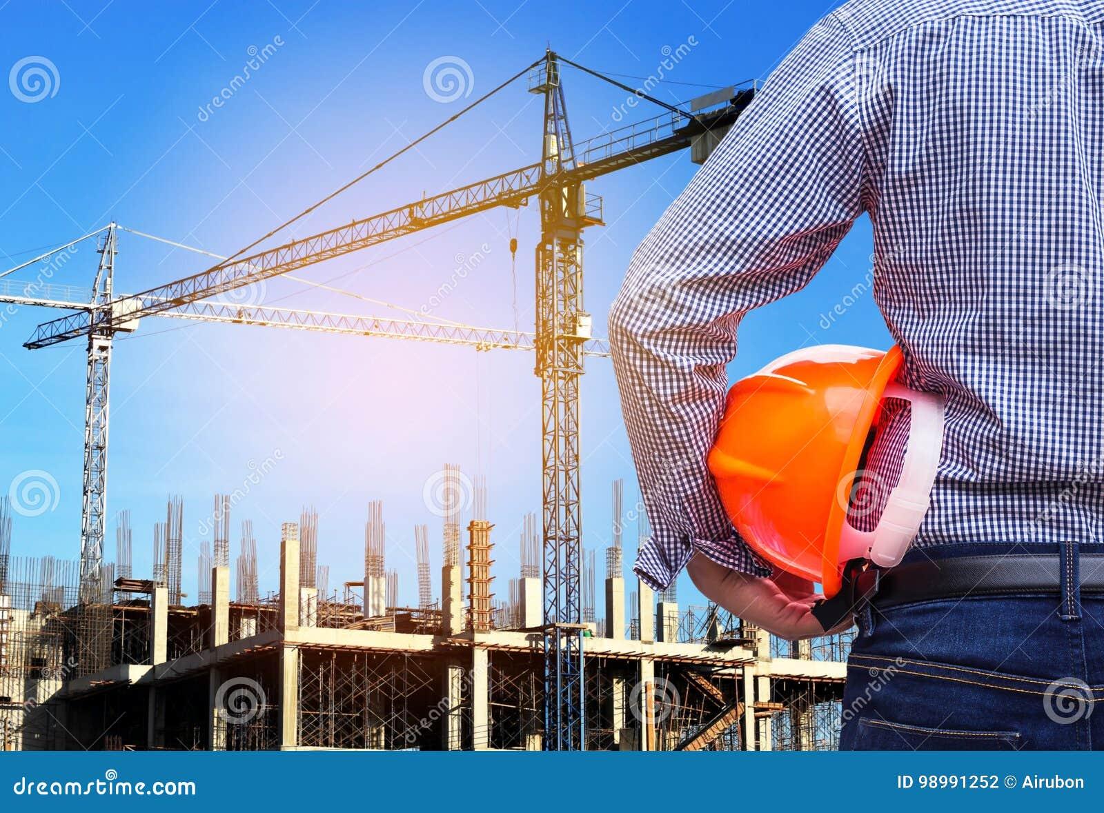 Konstruuje mienie żółtego zbawczego hełm w budynek budowie z żurawiem