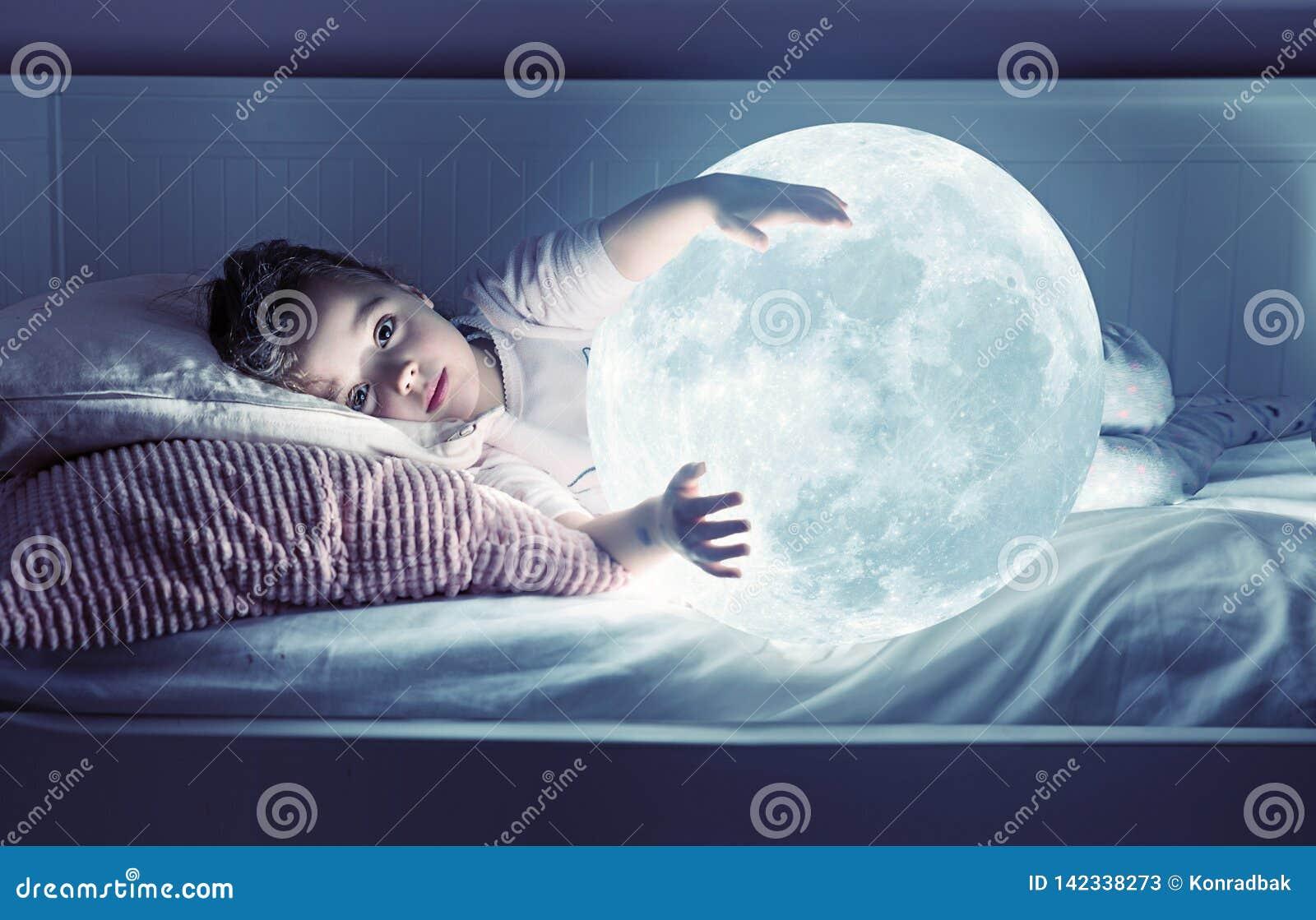 Konststående av en gullig liten flicka som rymmer en måne