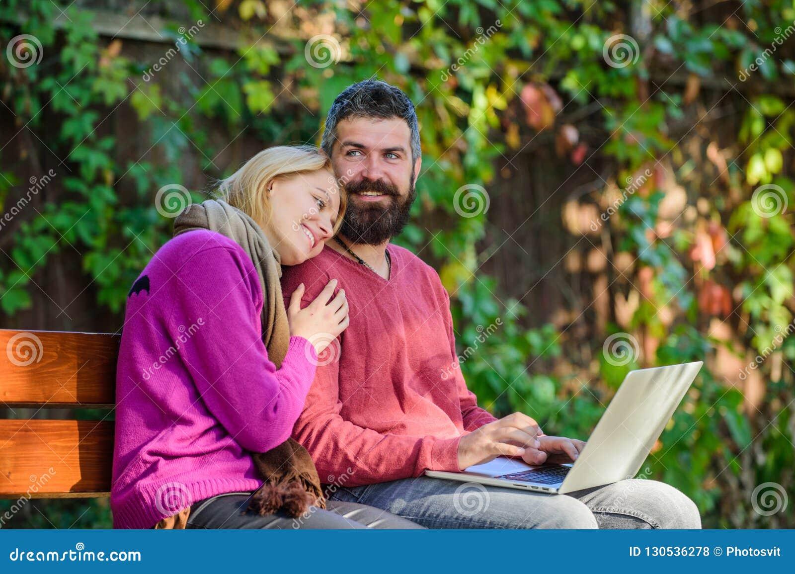 Konsumerar den förälskade anteckningsboken för par innehållet Internet som surfar begrepp Par med bärbara datorn sitter bänken pa