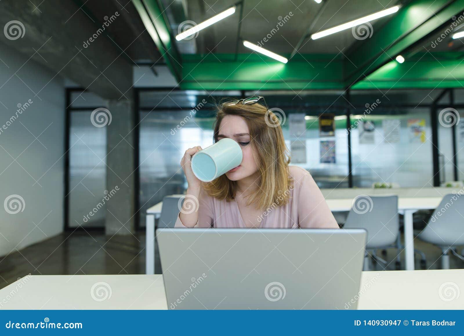 Kontorsarbetaren dricker kaffe, medan arbeta på en dator Flickan dricker en varm drink från rånar och använder en bärbar dator