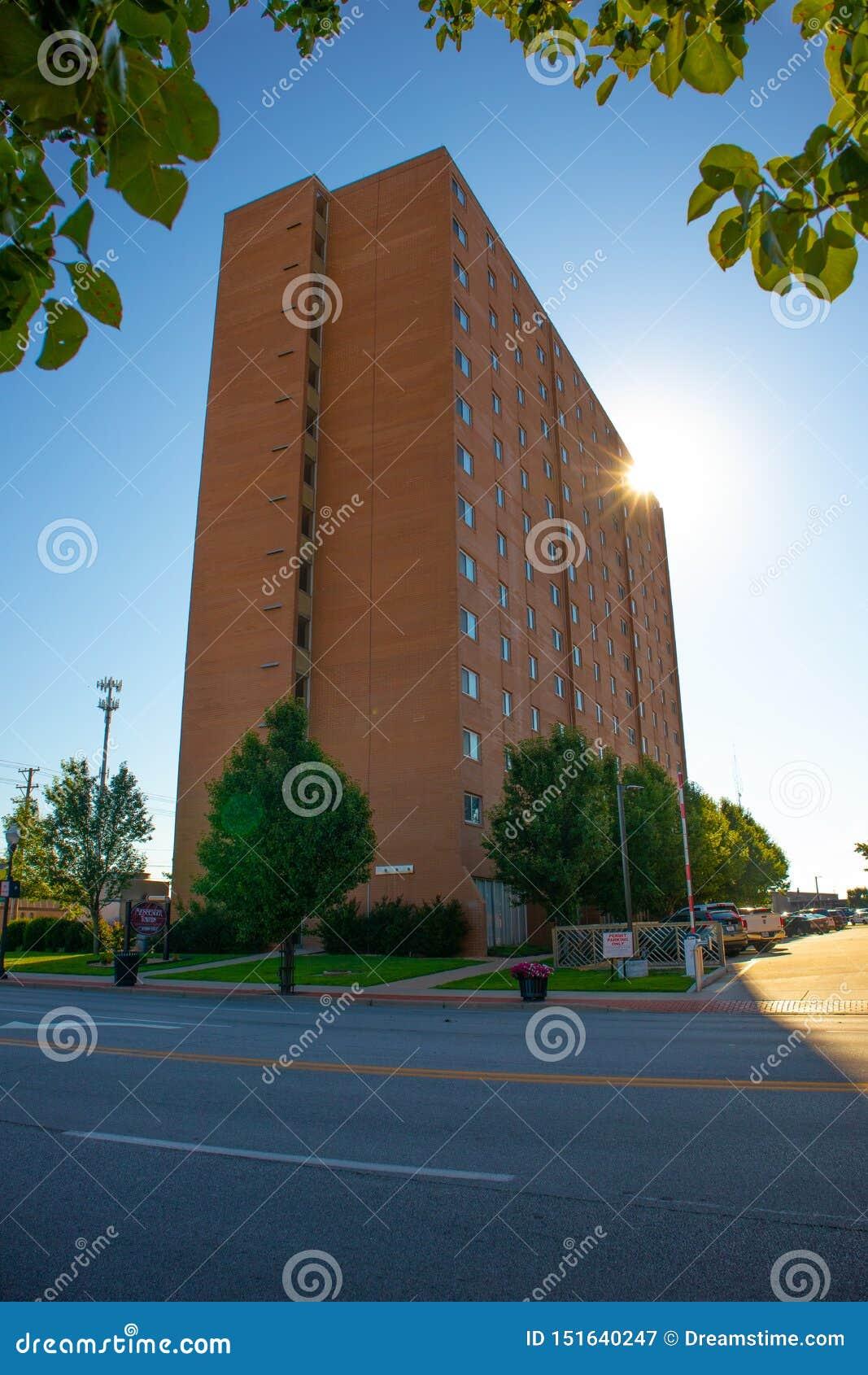 Kontorsbyggnad för röd tegelsten med solen bak den