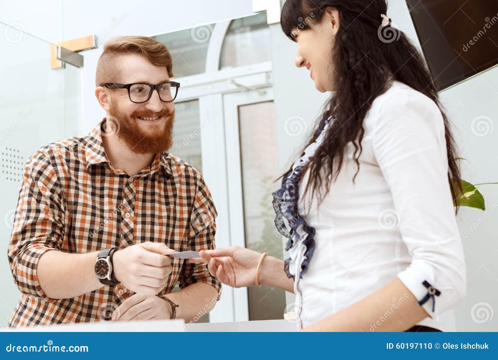Kontorschef som ger kunden ett affärskort