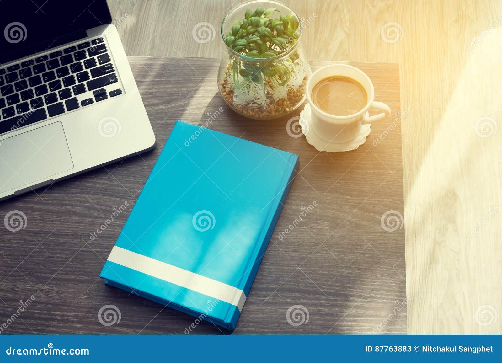 Kontorstabell med för blåtträkning för tom skärm boken, nytt kaffe och