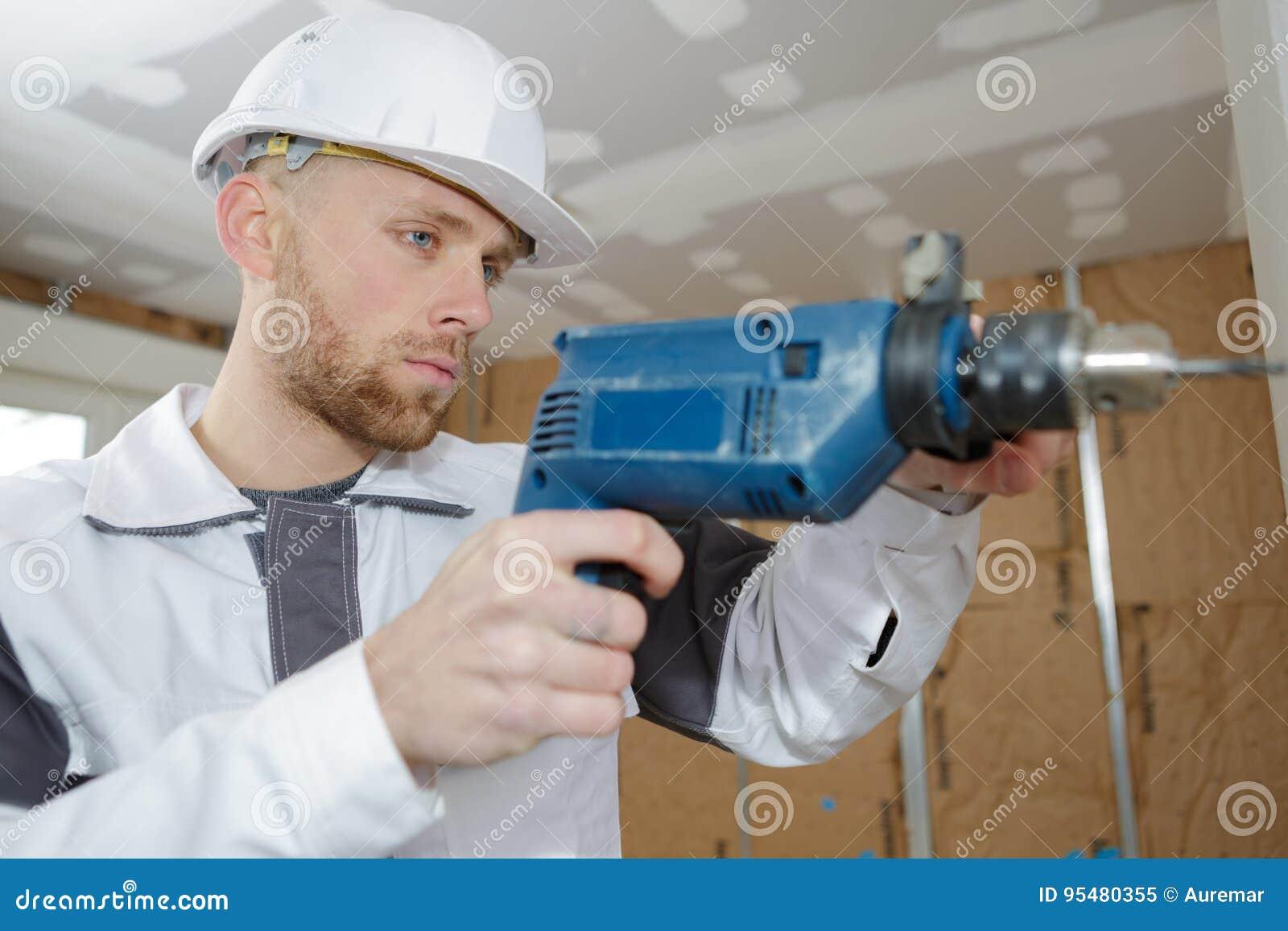 Kontrahent używa młoteczkowego świder musztrować betonową ścianę