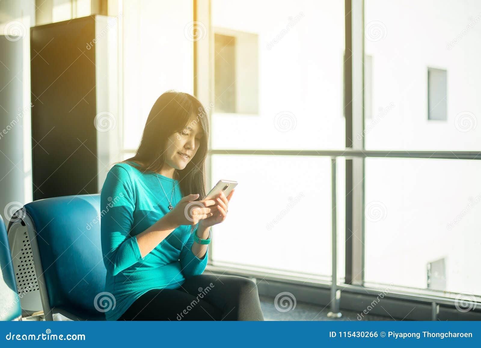 Kontrollerar reser den hållande mobiltelefonen för den asiatiska kvinnapassageraren och det kontrollerande flyget eller online- i