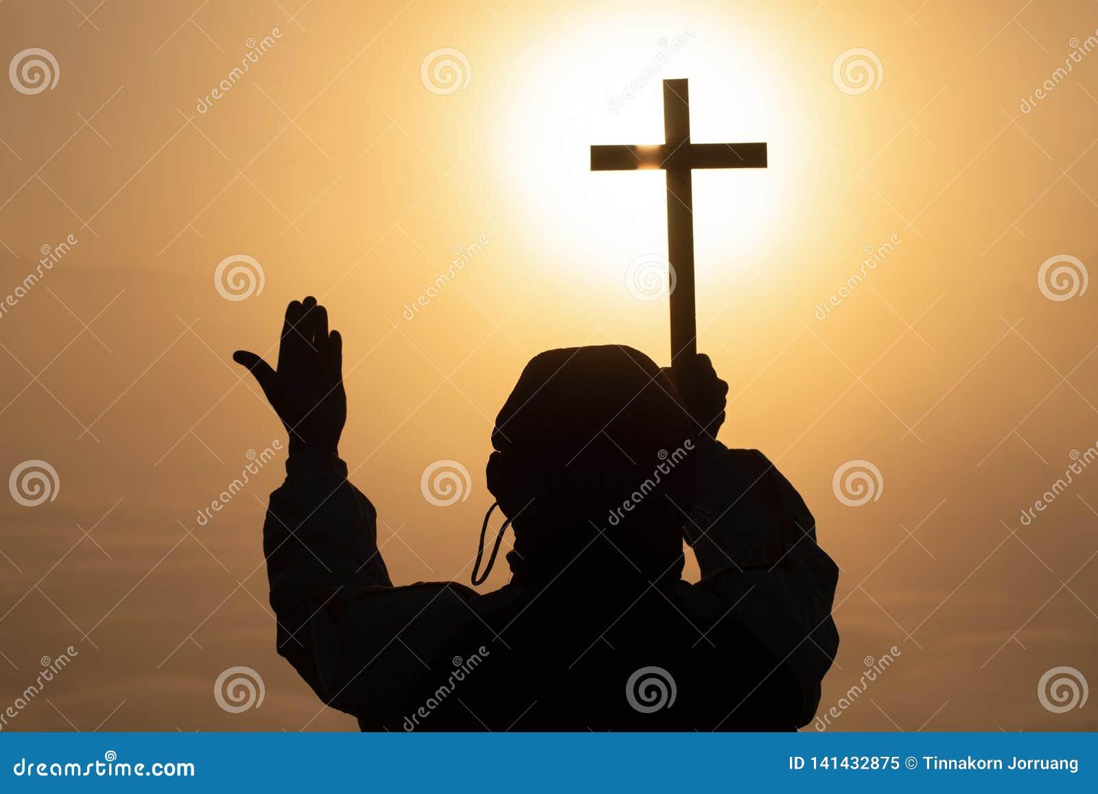 Kontur av den kristna mannen som rymmer ett kors, kors i händer som ber för välsignelsen från gud på solljusbakgrund, hoppbegrepp